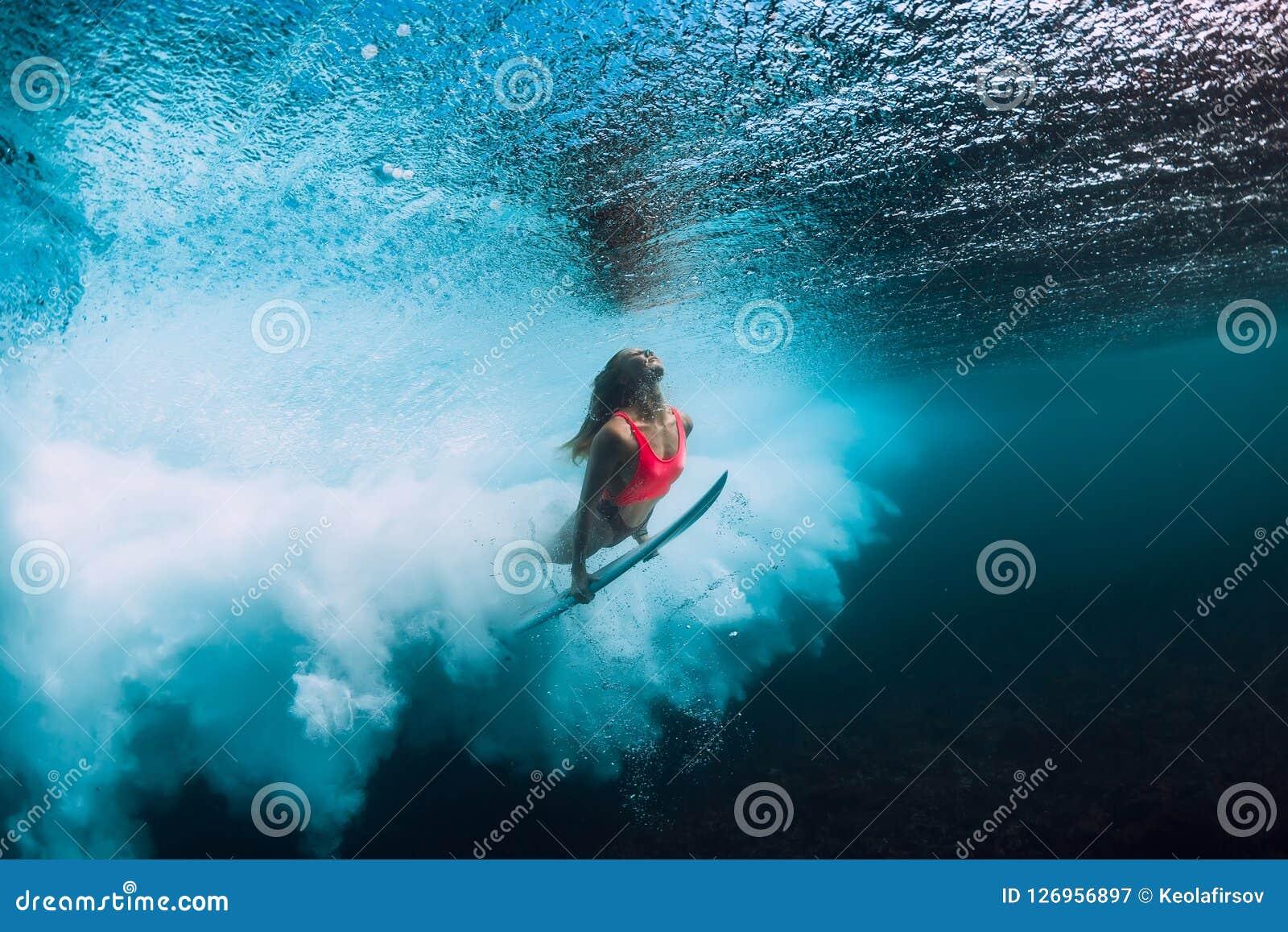 Surferfrau mit dem Surfbretttauchen Unterwasser mit Untermeereswogen
