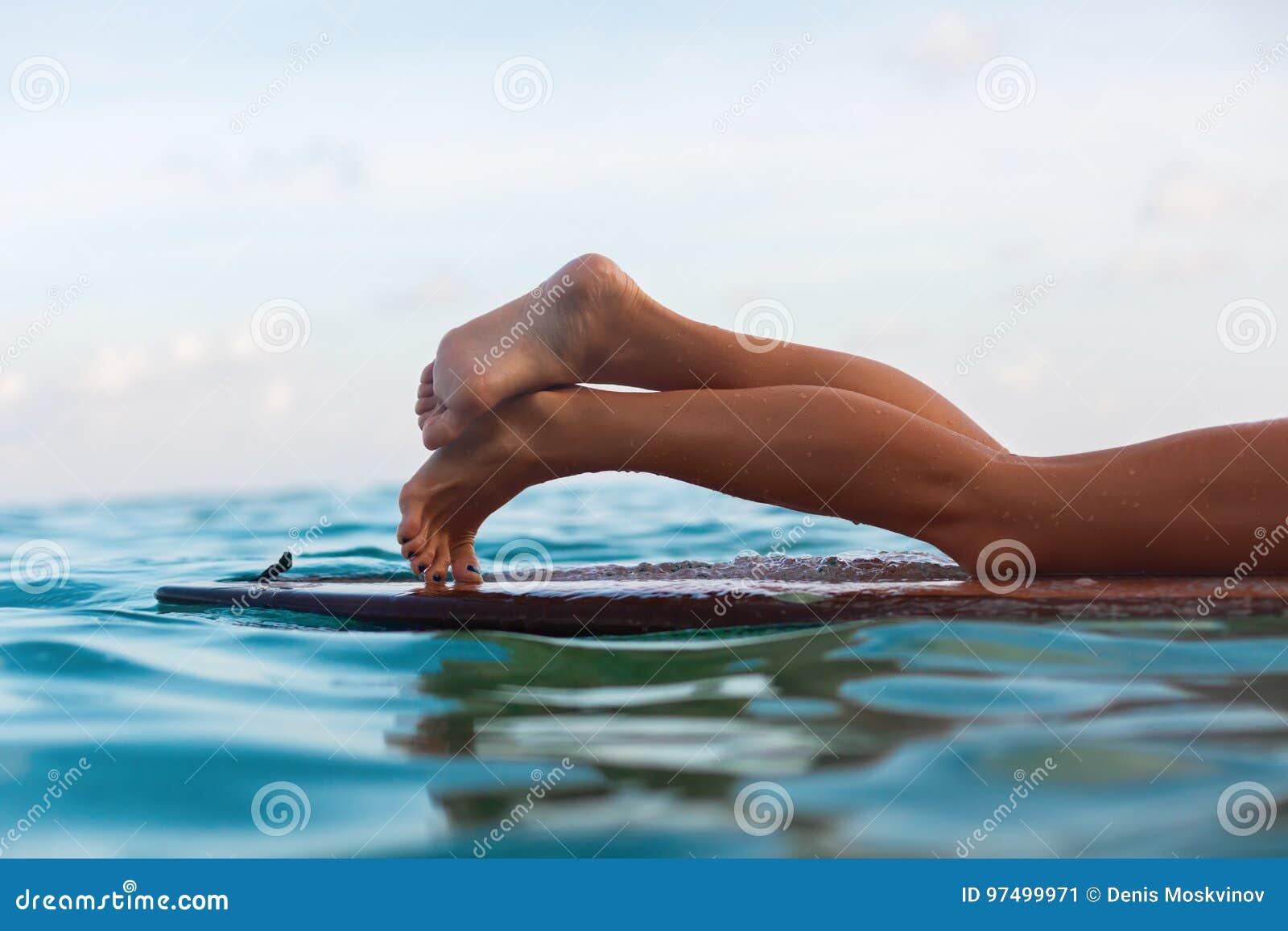Surfermeisje die op surfplank liggen