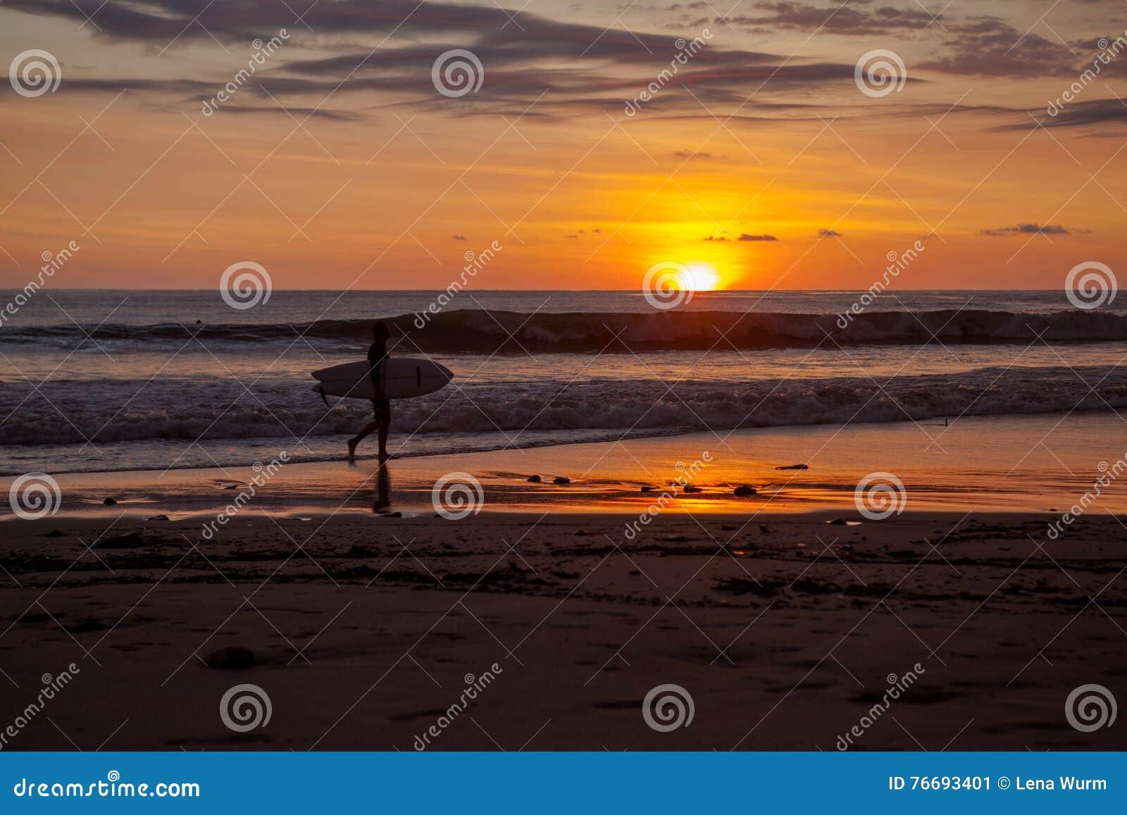 Surfers στην παραλία Santa Τερέζα στο ηλιοβασίλεμα/τη Κόστα Ρίκα