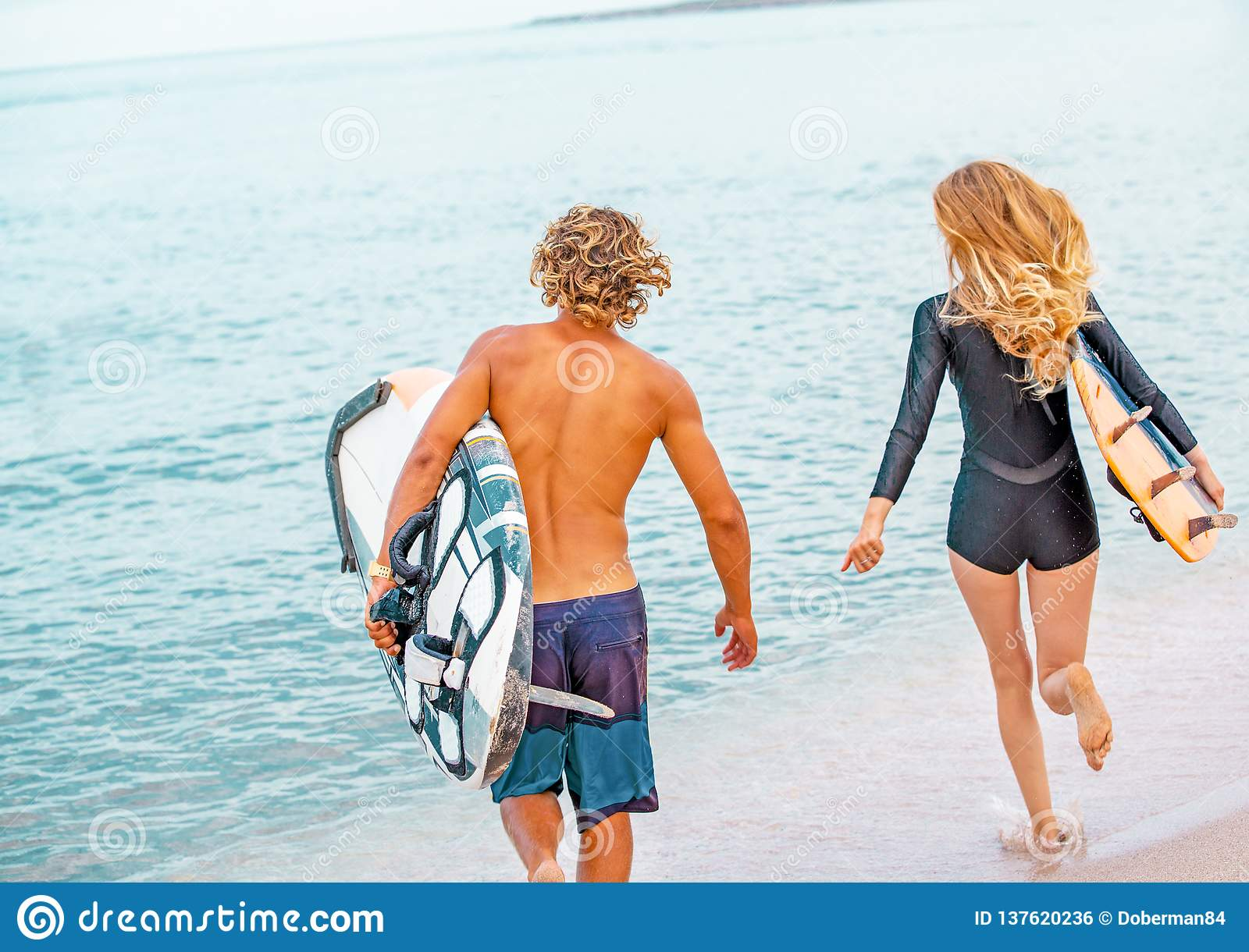 Surfers at the beach- Smiling couple of surfers run on the sea and having fun in summer. Extreme sport and vacation