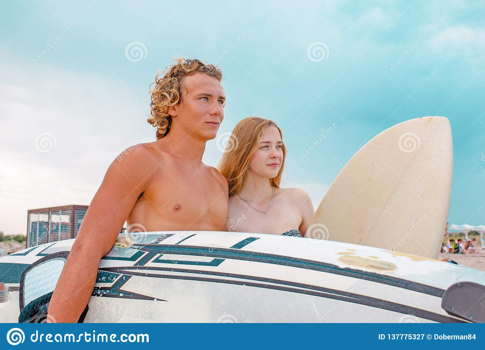 Surfers at the beach- Smiling couple of surfers walking on the beach and having fun in summer. Extreme sport and