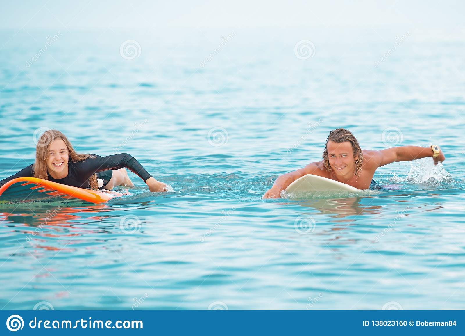 Surfers at the beach- Smiling couple of surfers swiming and having fun in summer. Extreme sport and vacation concept