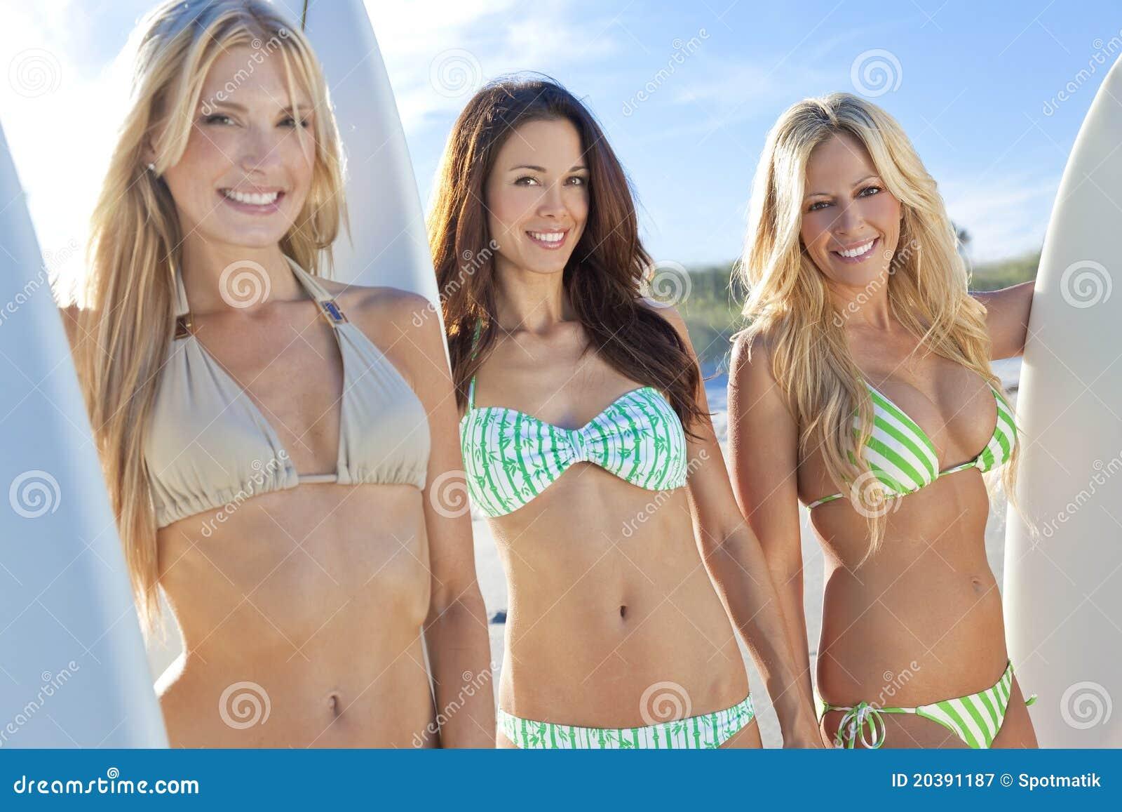 Surfers de femmes dans des bikinis avec des planches de surfing chez Beac