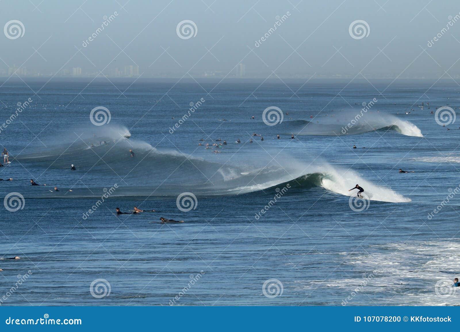 Surfers In The Ocean Off The Coast Of Huntington Beach California