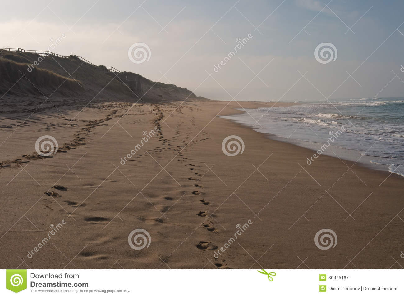 Surfing beach in morning dusk with breaking waves footprints on sand