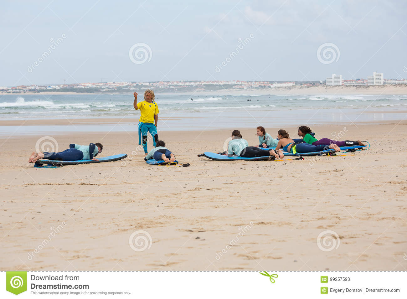 Surfing Coach Instructs Novice Surfers On The Beach Near ...