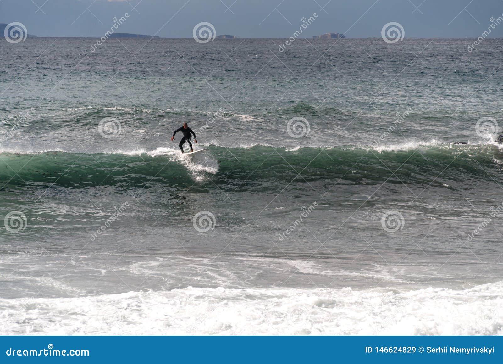 Surfingowiec bierze fal? na surfboard, obruszenia wzd?u? fali w tle g?ra, Sorrento W?ochy