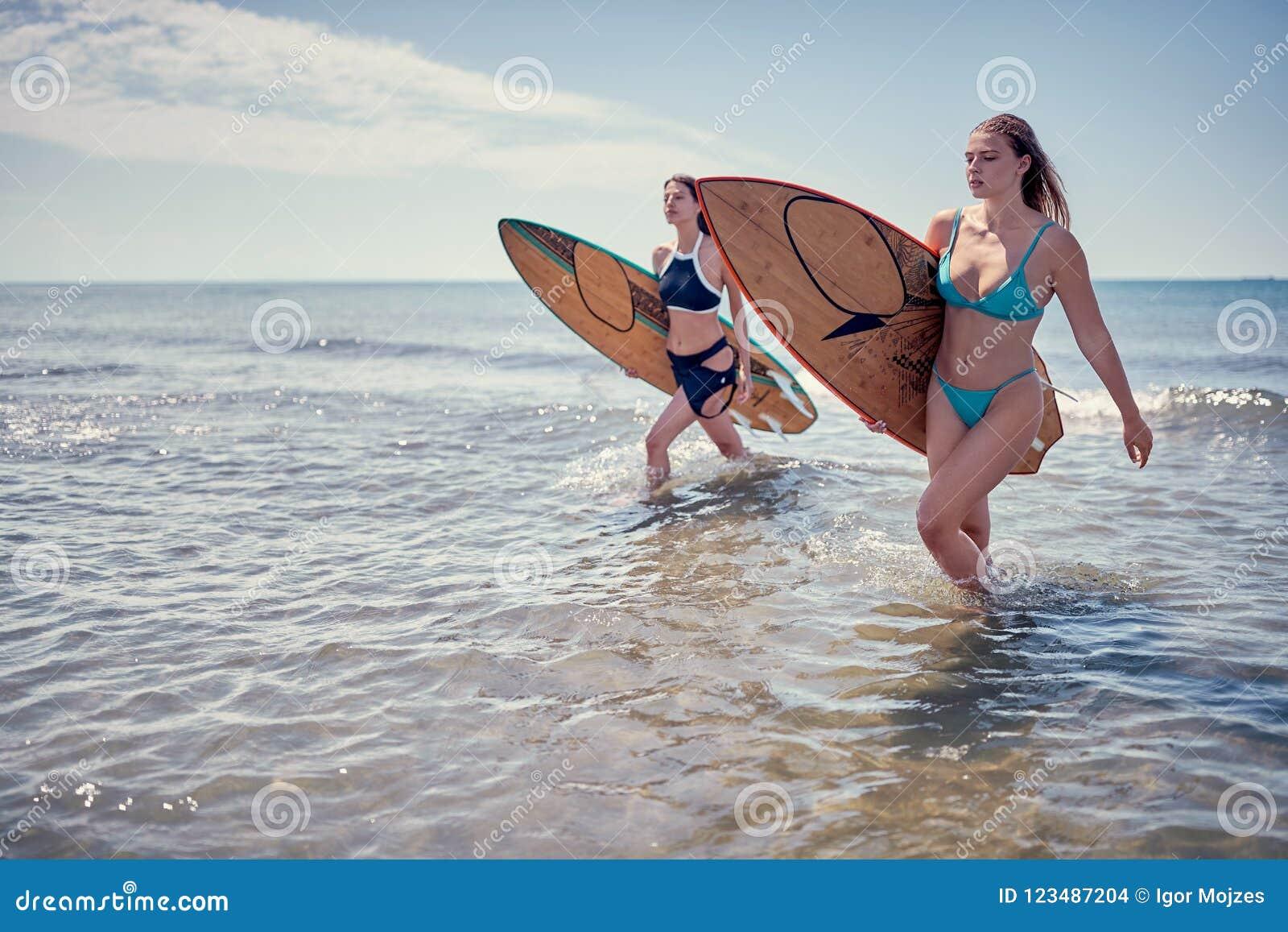 Surfingowiec dziewczyny odprowadzenie z deską Surfingowiec dziewczyna Piękny Młody Wom
