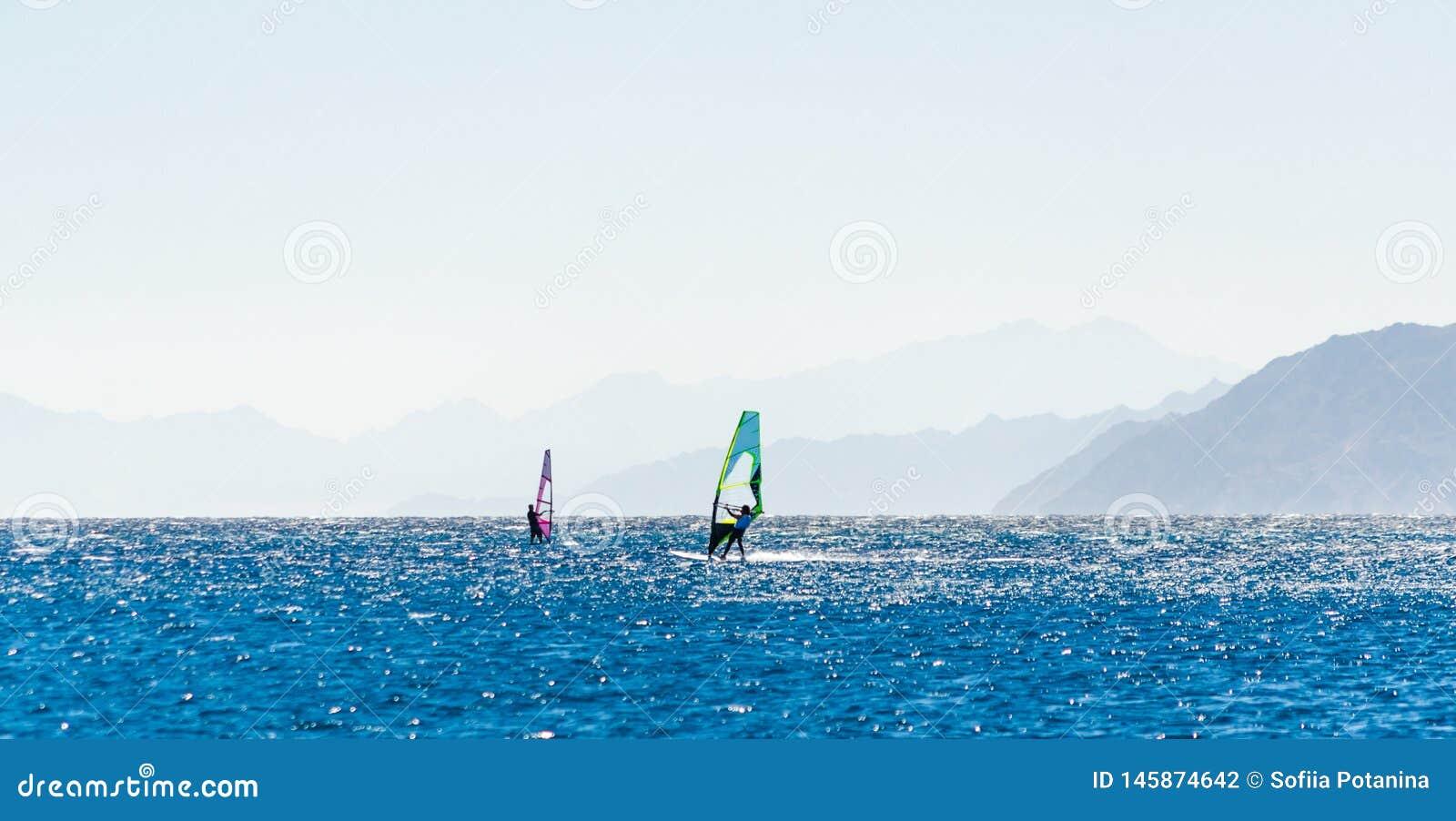 Surfingowowie jadą w Czerwonym morzu w Egipt przeciw tłu skalisty wybrzeże