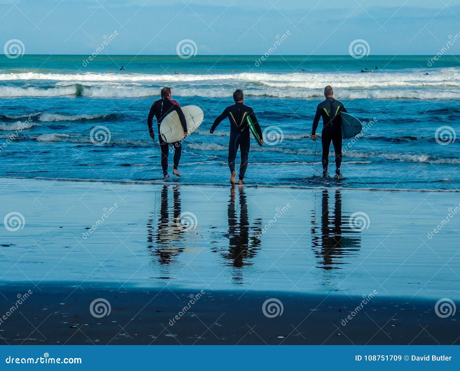 Surfingowowie na Piha plaży, Auckland, Nowa Zelandia