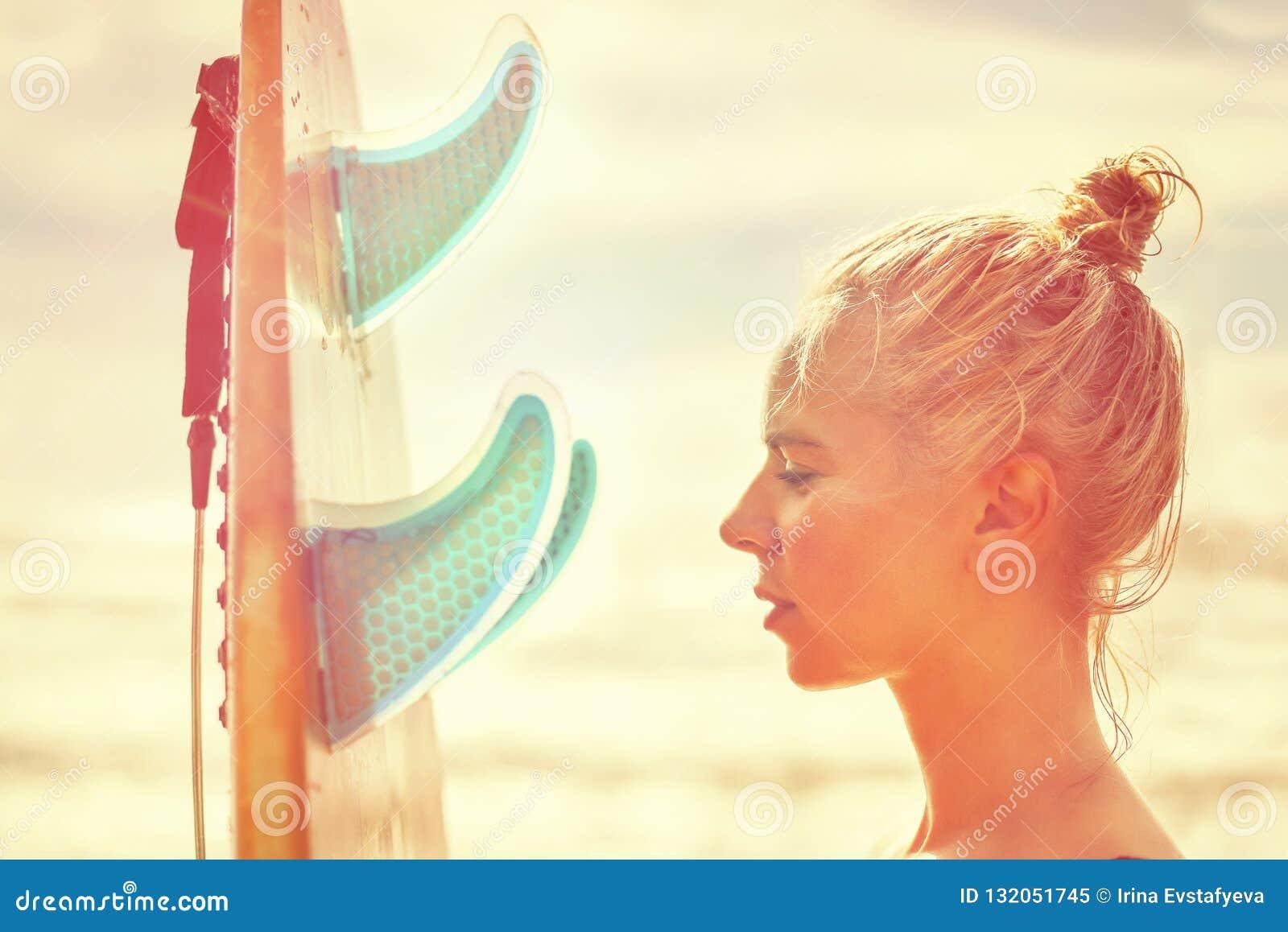 Surfista bonito da menina com uma placa no nascer do sol Férias de verão no mar, estilo de vida saudável