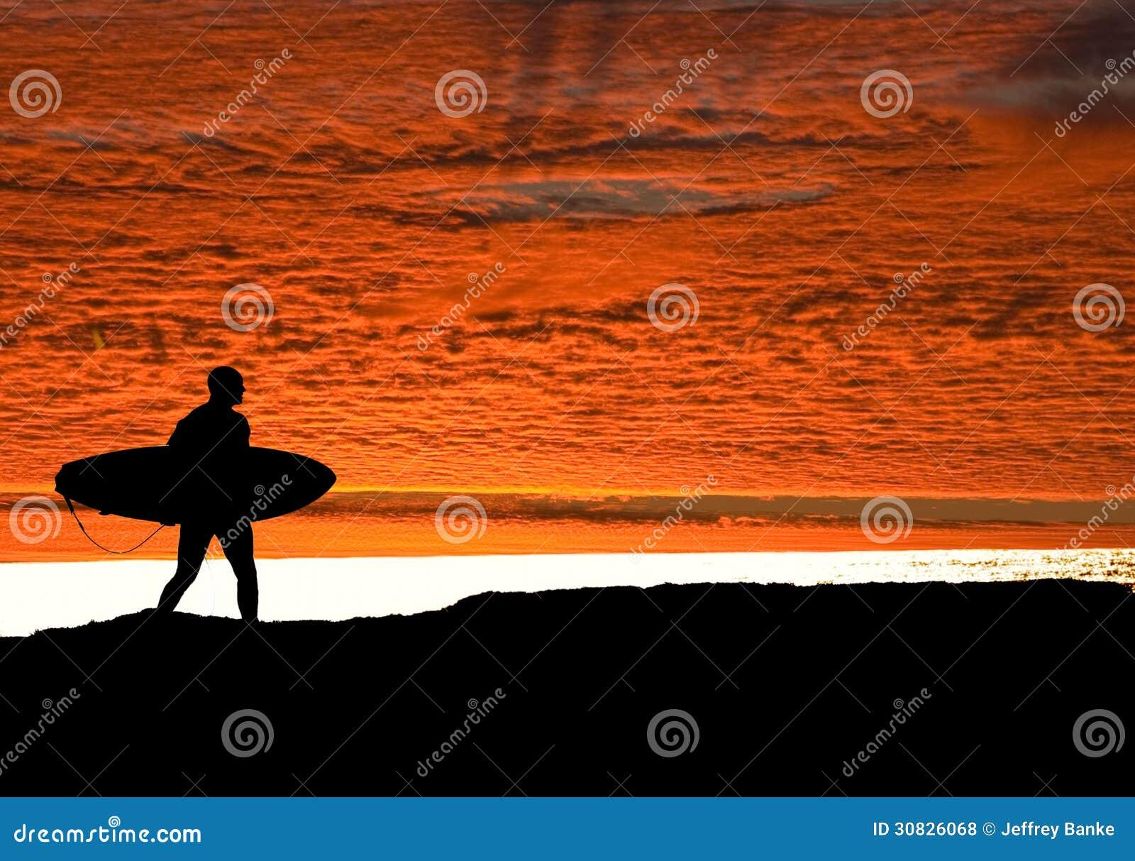 Surfista che si dirige verso oceano come gli insiemi del sole