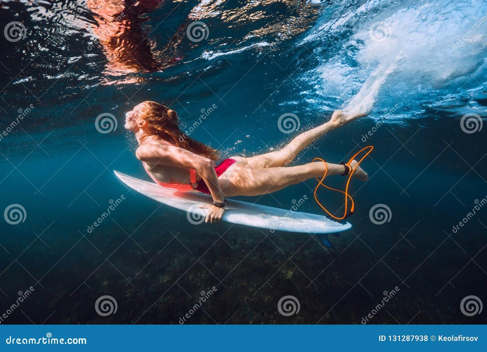 Surfista com mergulho da placa de ressaca debaixo d água com a onda de oceano grande inferior