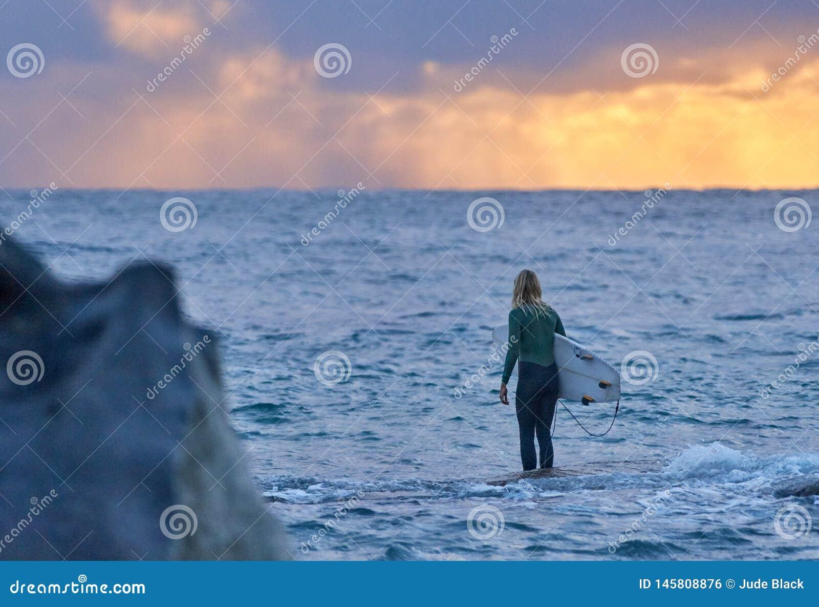 Surfista da jovem mulher que olha para fora ao mar