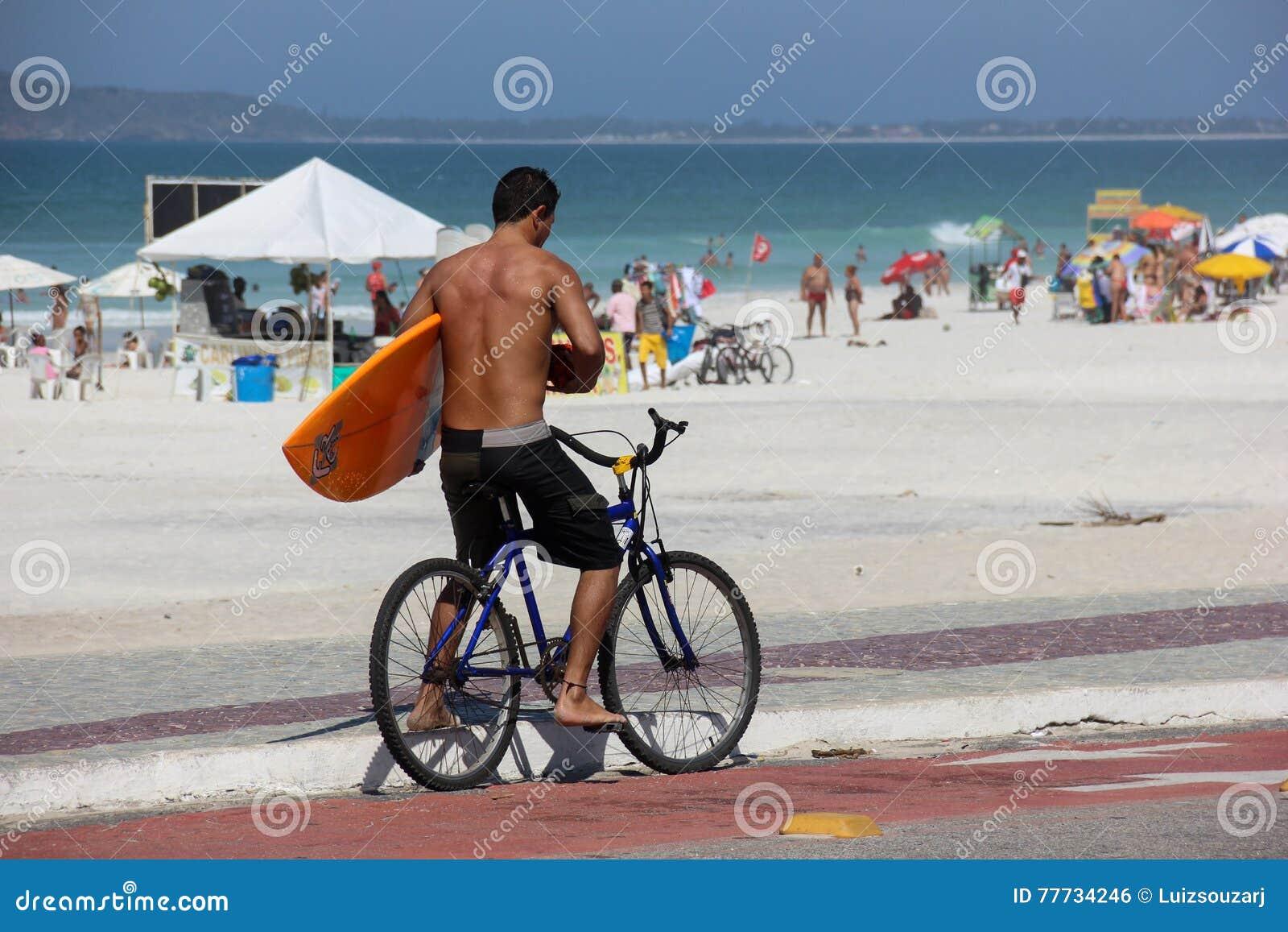 Surfista na bicicleta no dia ensolarado