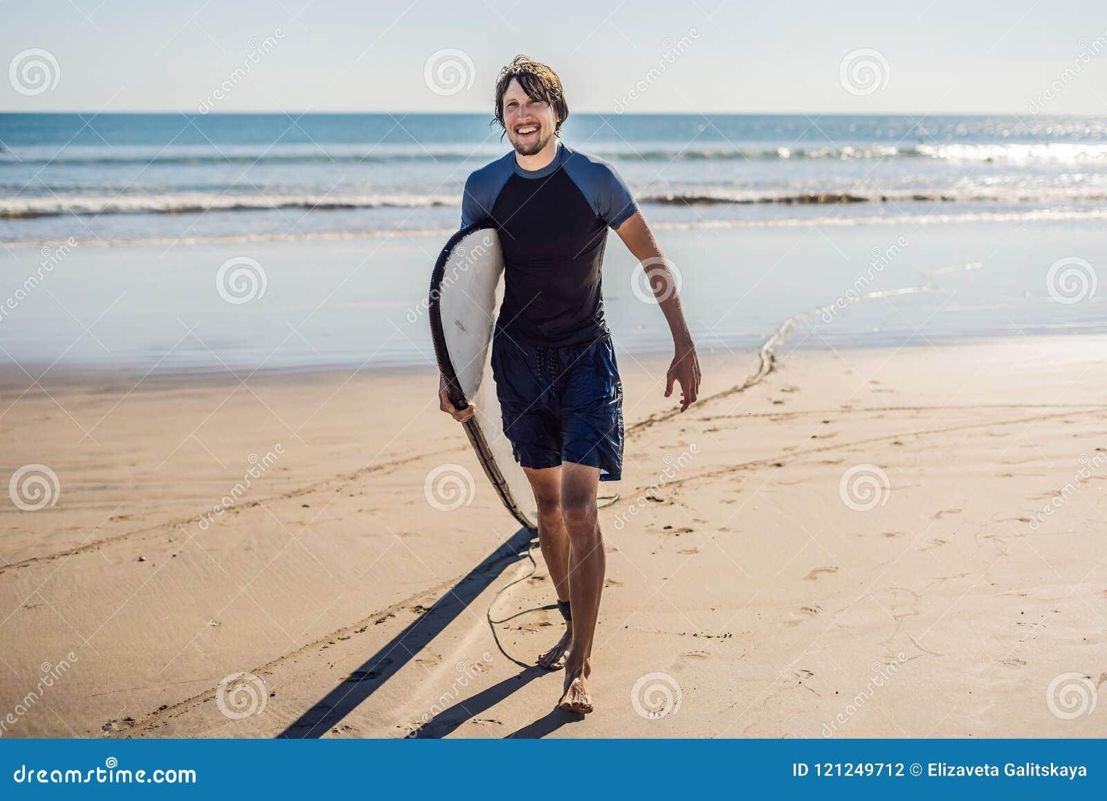 Surfista novo desportivo considerável que levanta com sua prancha sob o seu