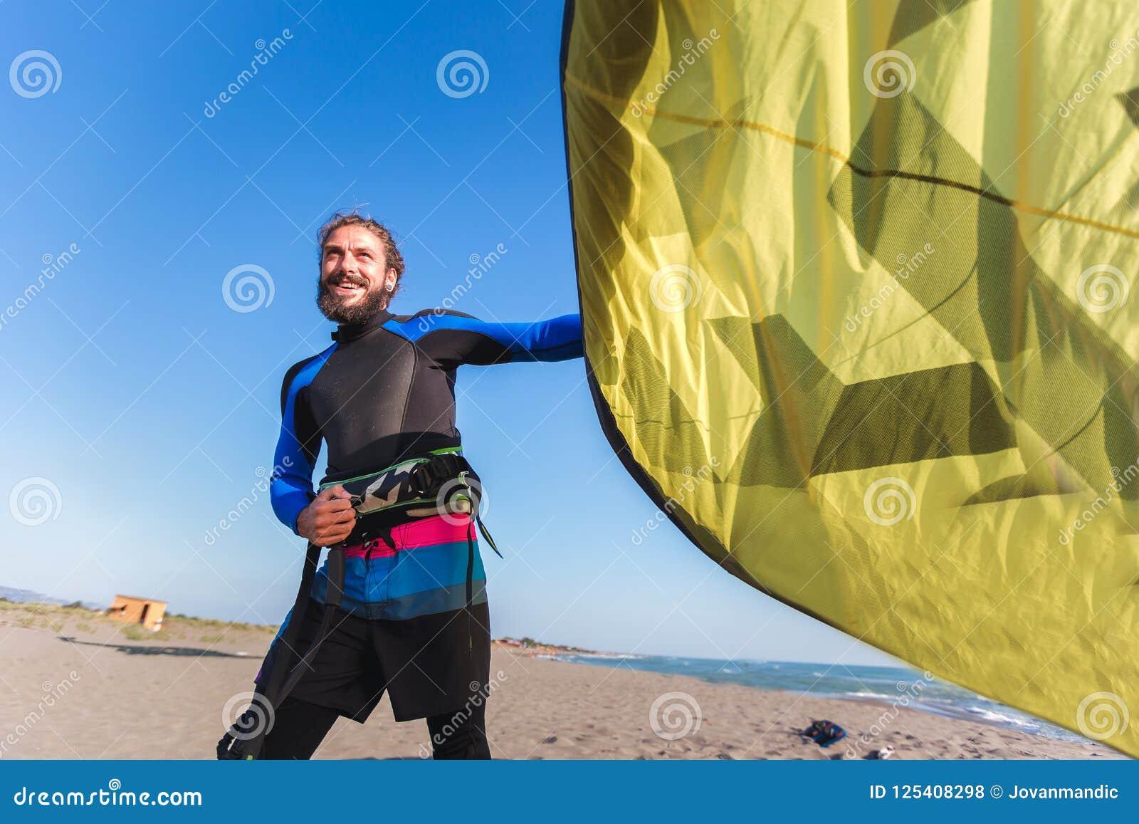 Surfista profissional do homem caucasiano que está no Sandy Beach com seu papagaio