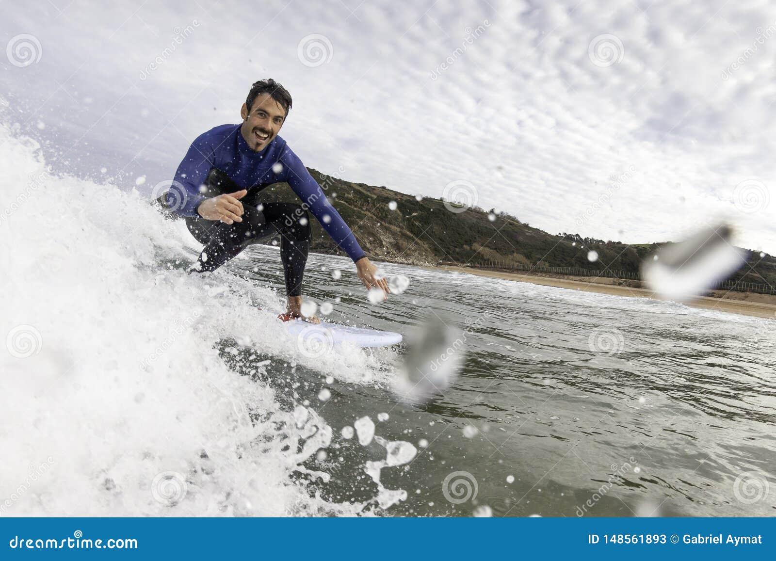 Surfista que tem o divertimento que trava uma onda e que cumprimenta