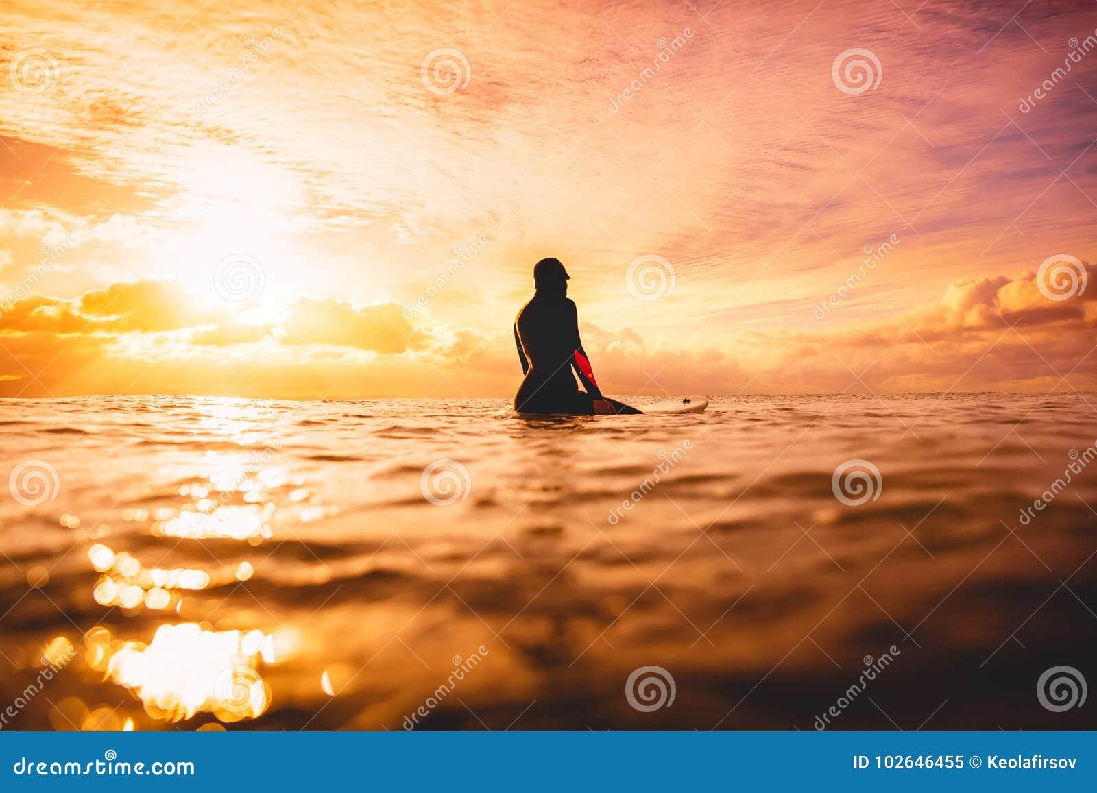 Surfuje dziewczyny w oceanie przy zmierzchem lub wschodem słońca Zima surfing w oceanie