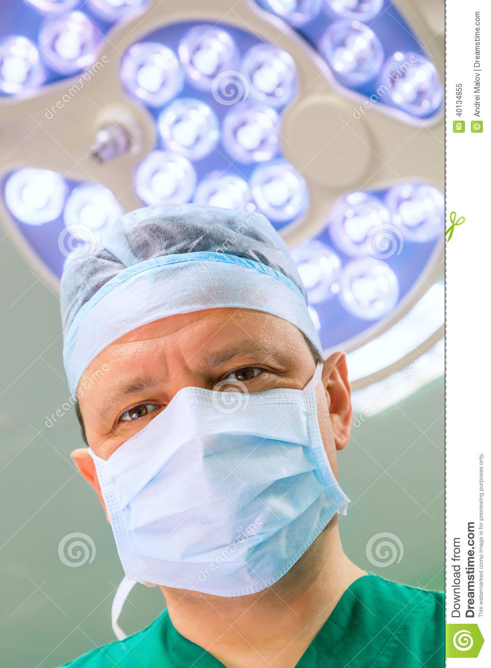 Surgeon in operation room with lamp on background.