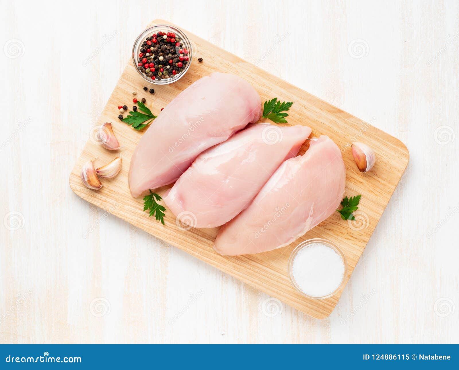 Surowa kurczak pierś polędwicowa z pikantność na drewnianej desce na białym drewnianym stole, odgórny widok
