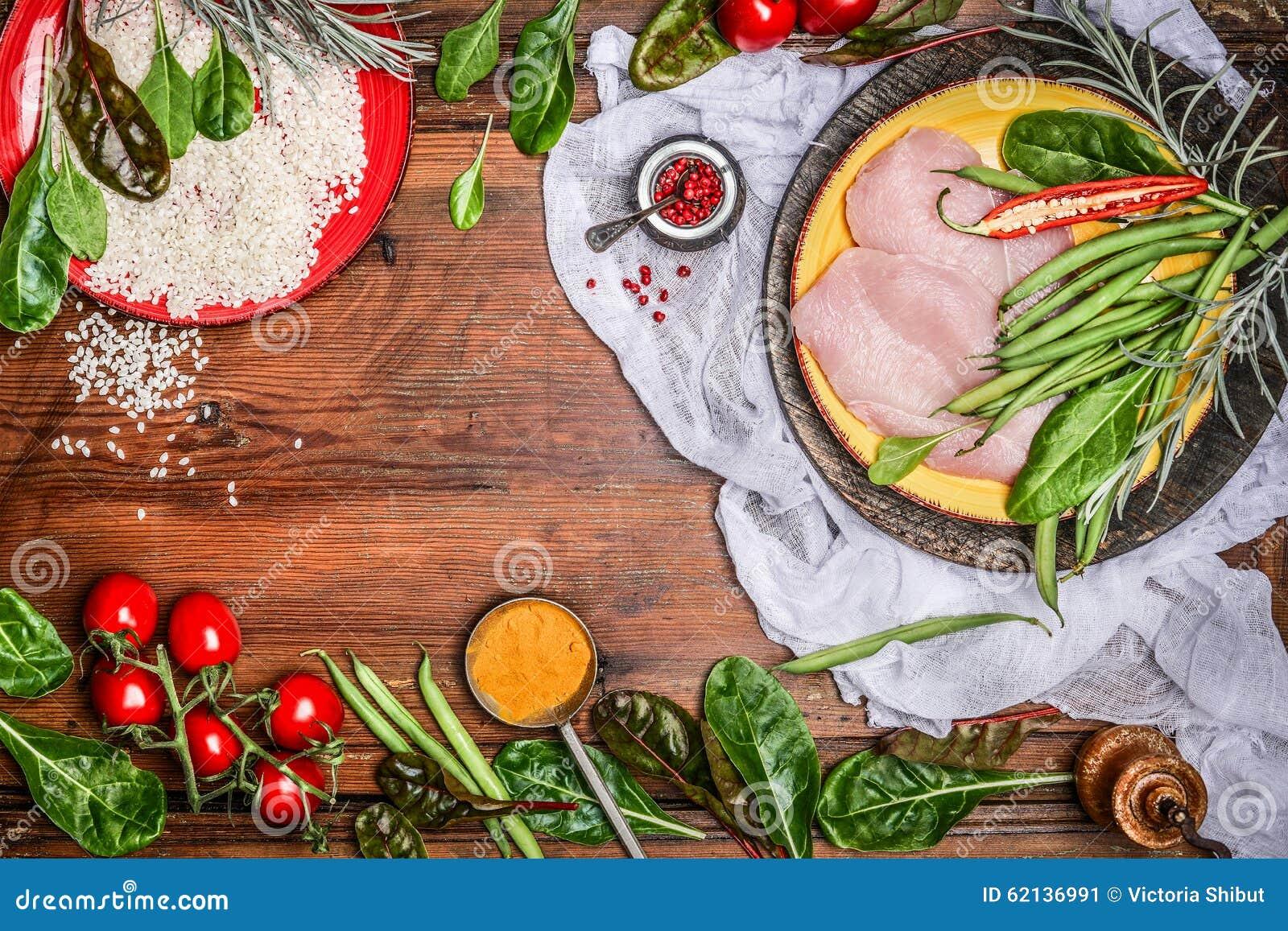 Surowa kurczak pierś z ryżowymi i świeżymi organicznie warzywo składnikami dla zdrowego kucharstwa na nieociosanym drewnianym tle