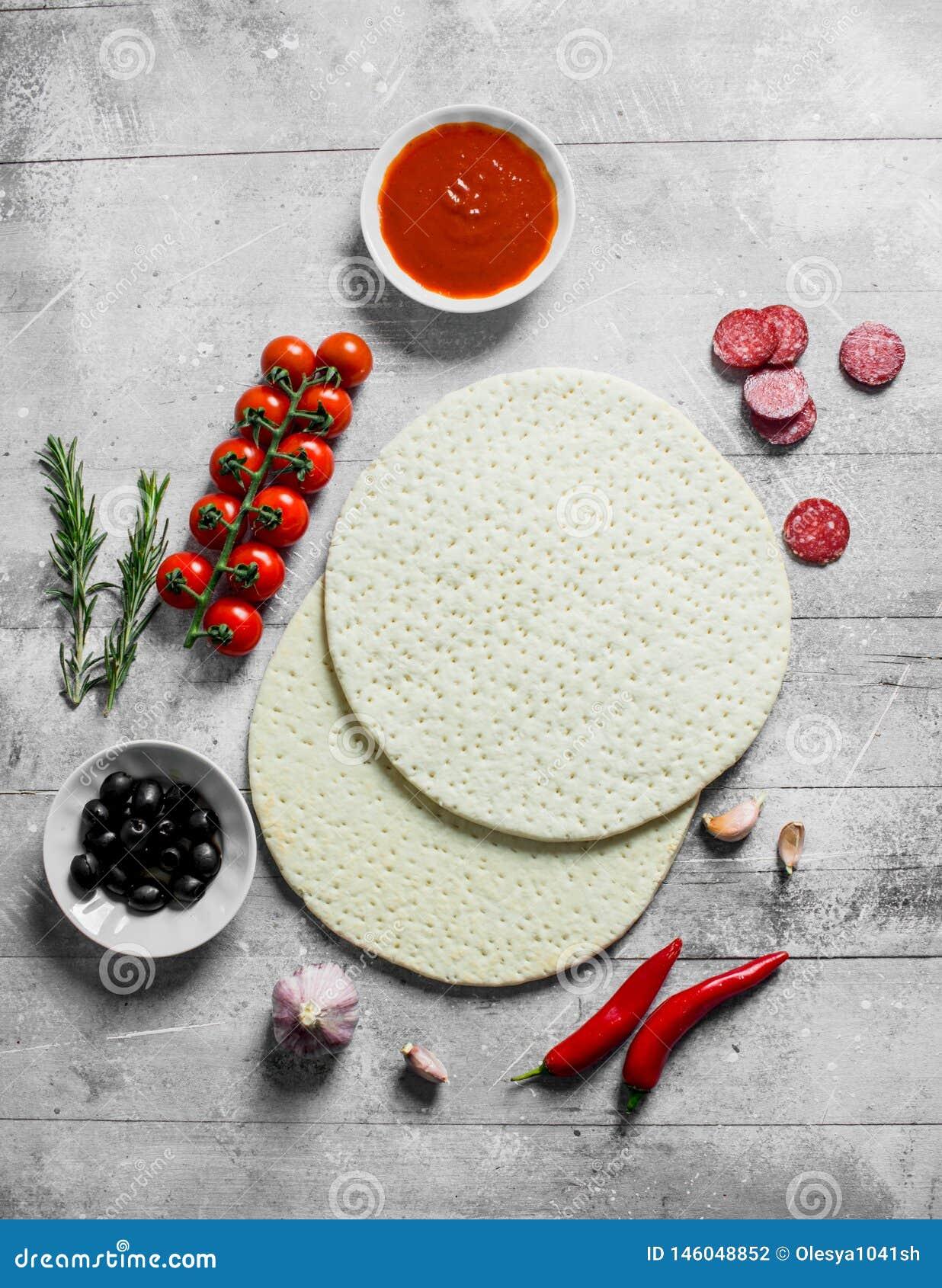 Surowa pizza Staczający się za round cieście z oliwkami, kiełbasami i pomidorami,