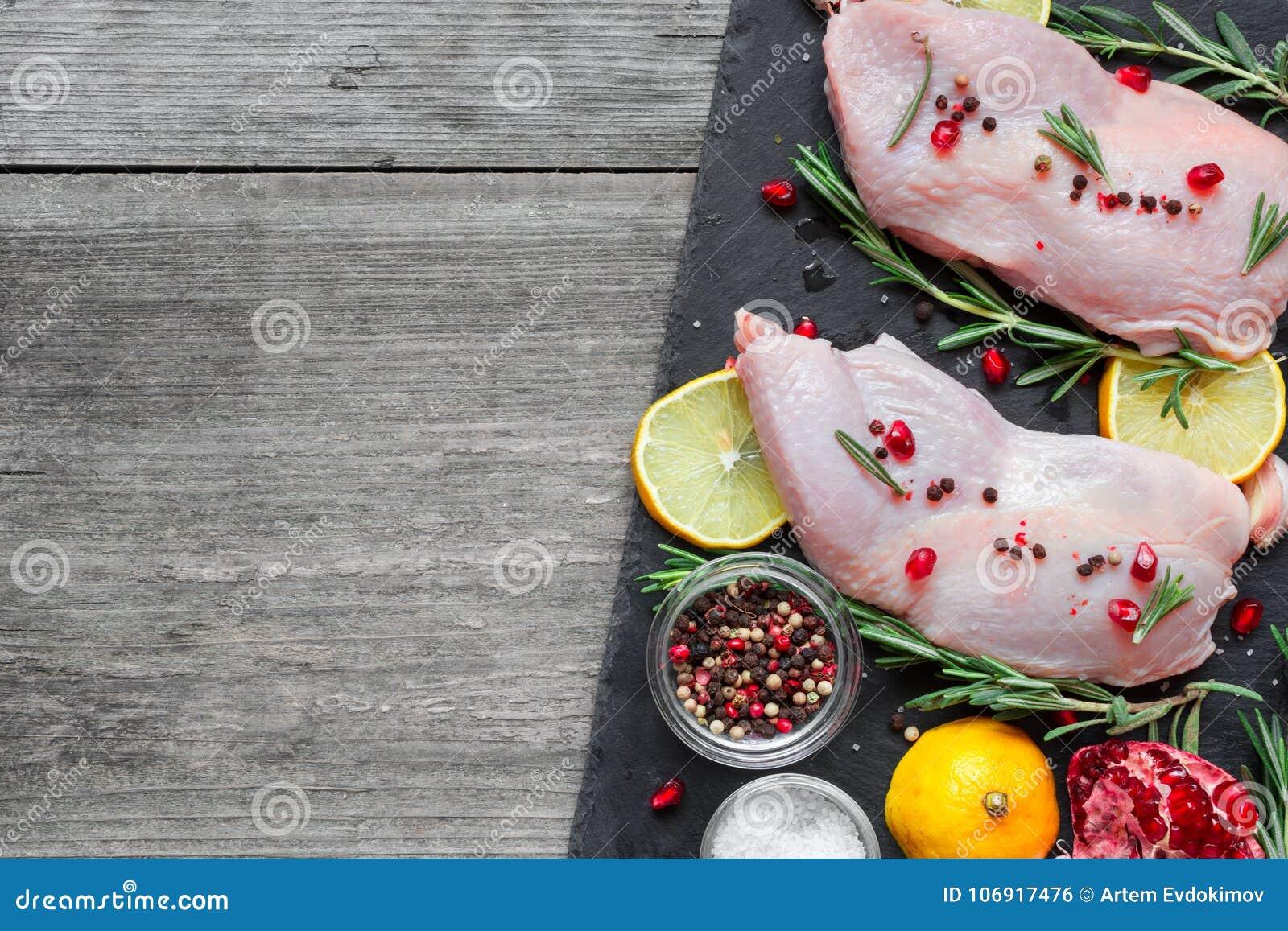 Surowe kurczak nogi z ziele, pikantność, cytryną i granatowem na zmroku łupku tnącej desce,