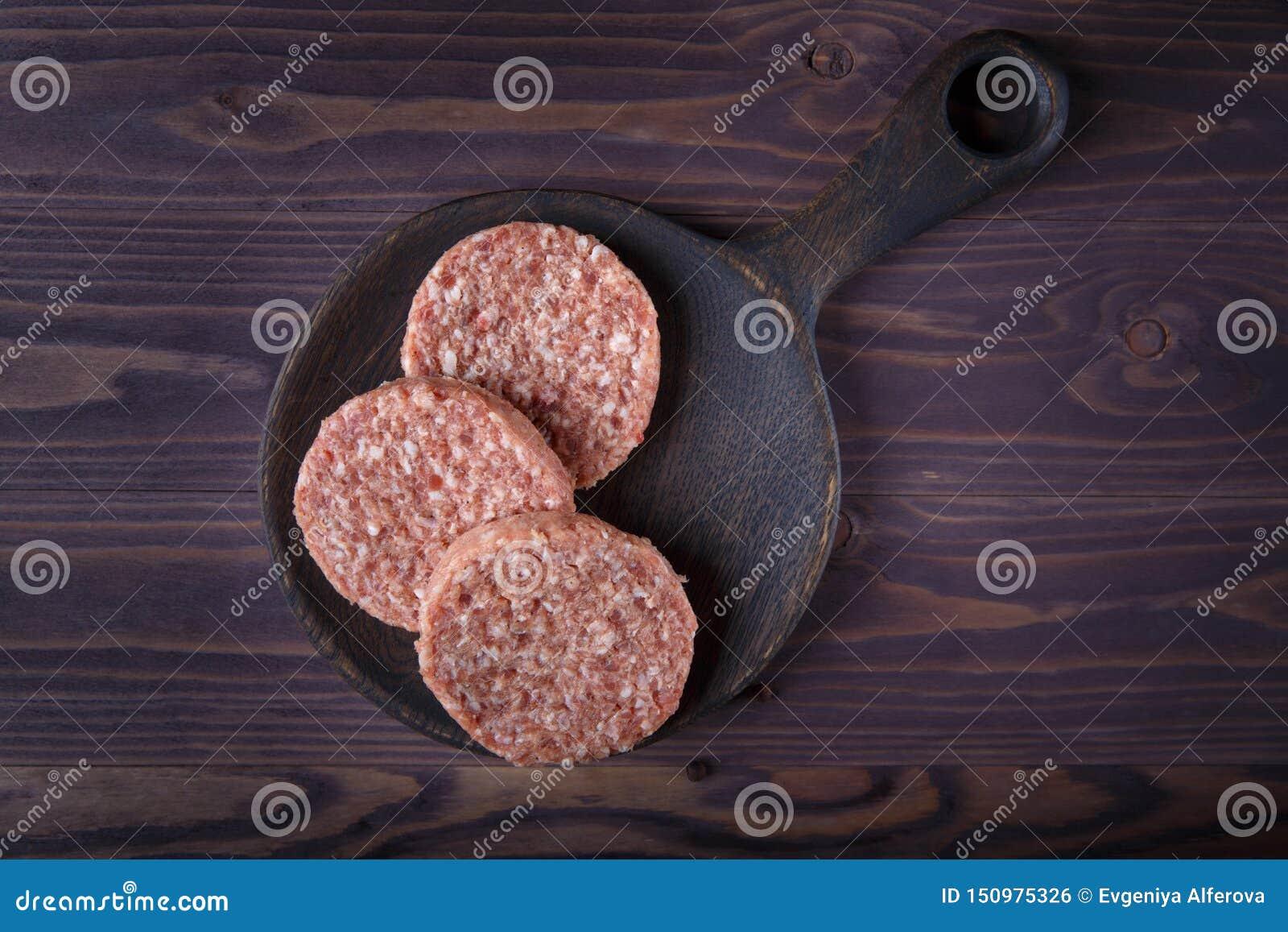 Surowej minced wo?owiny hamburgeru mi??ni cutlets na ciemnym drewnianym tle