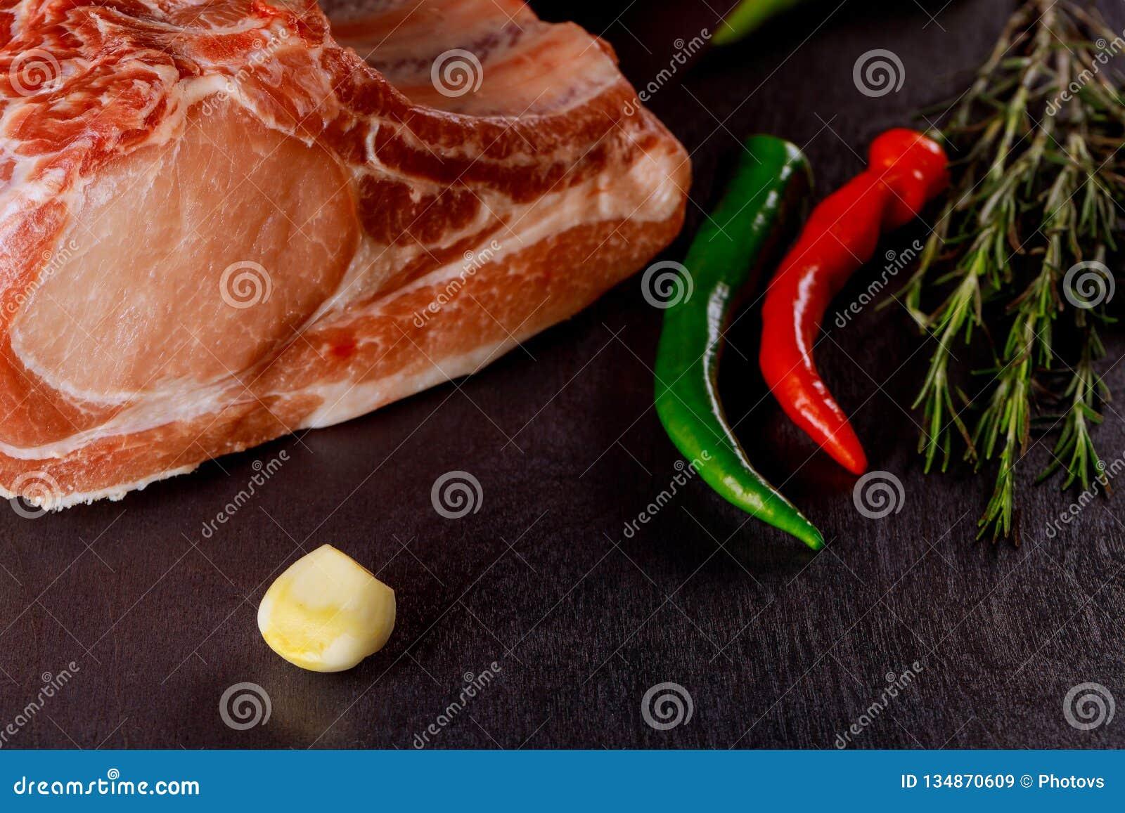 Surowi wieprzowina kotleciki z ziele i pikantność na tnącej desce Przygotowywający dla gotować