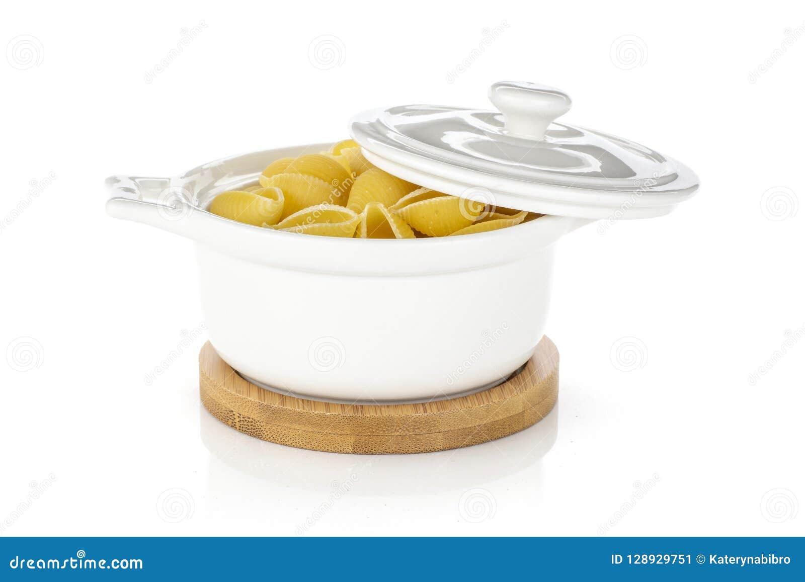 Surowy żółty makaronu conchiglie odizolowywający na bielu