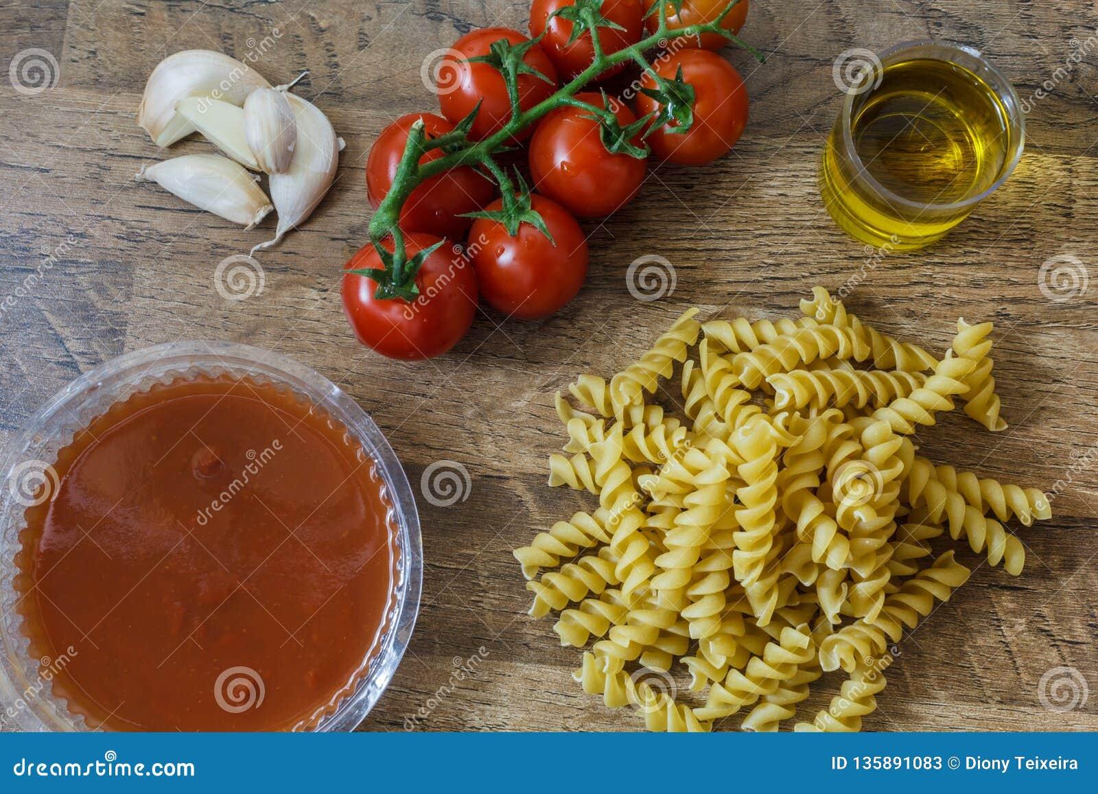 Surowy makaron i składnika kluski, czereśniowi pomidory, oliwa z oliwek, czosnek dla robimy tradycyjnemu włoskiemu jedzeniu