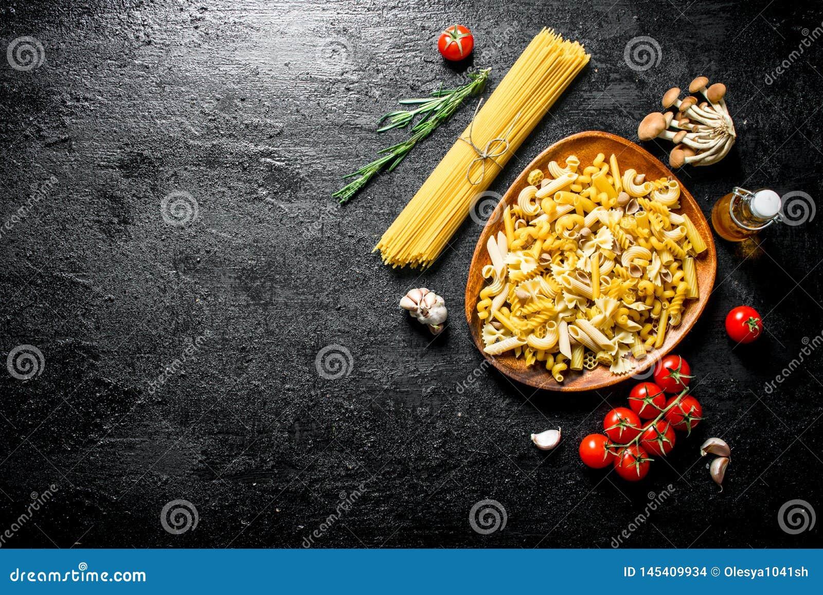Surowy makaronu asortyment z rozmarynami, pomidorami i pieczarkami,