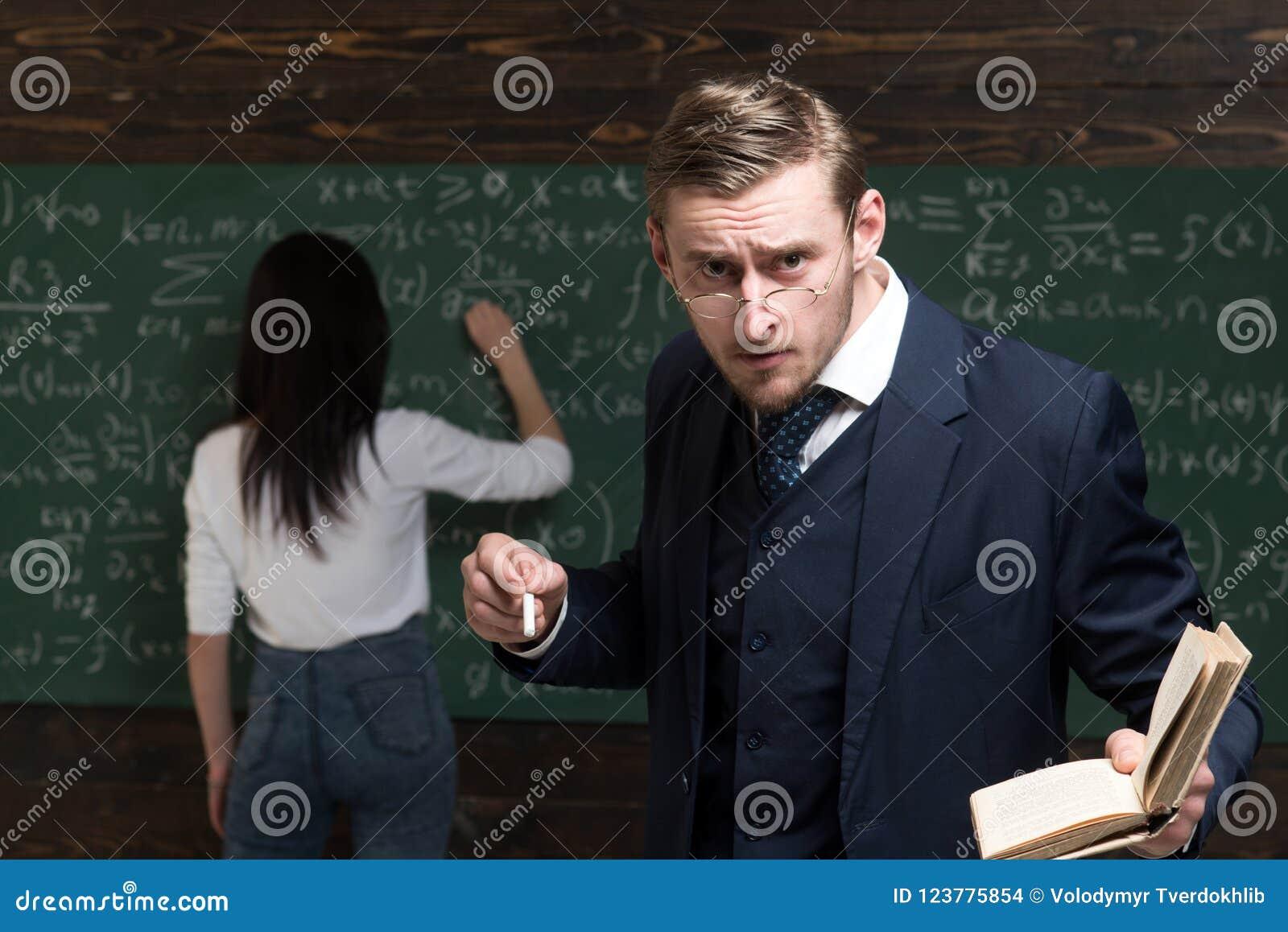 Surowy profesor patrzeje uczni nad szkłami podczas gdy trzymający książkę i kawałek kreda w jego ręki samica ucznia