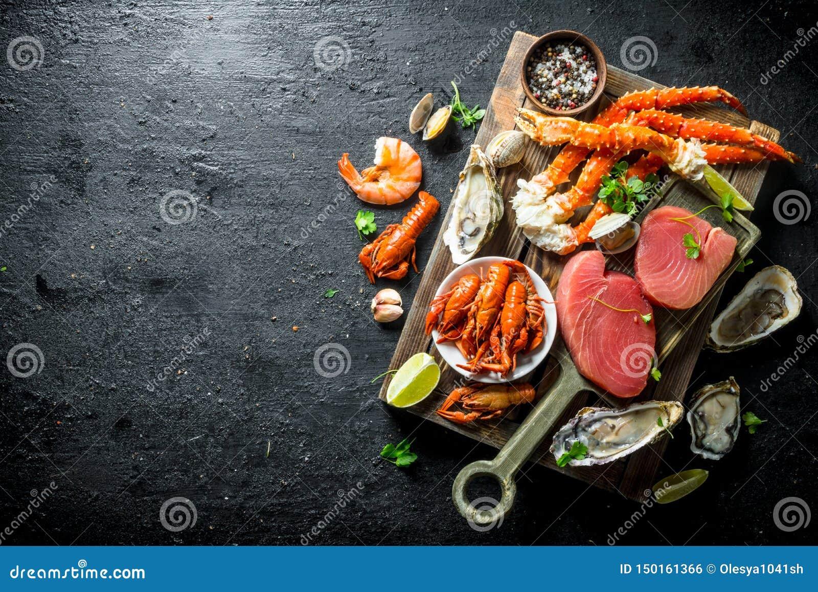 Surowy tuńczyka stek, owoce morza na drewnianej tacy i
