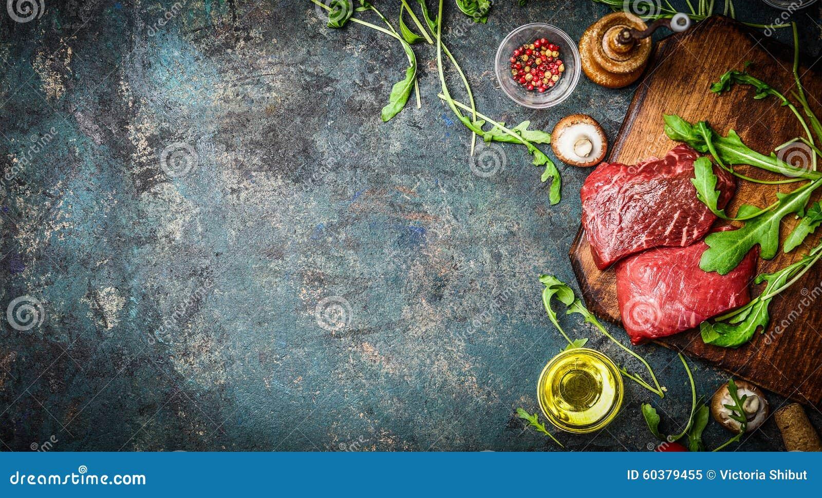Surowy wołowina stek i świezi składniki dla gotować na nieociosanym tle, odgórny widok, sztandar