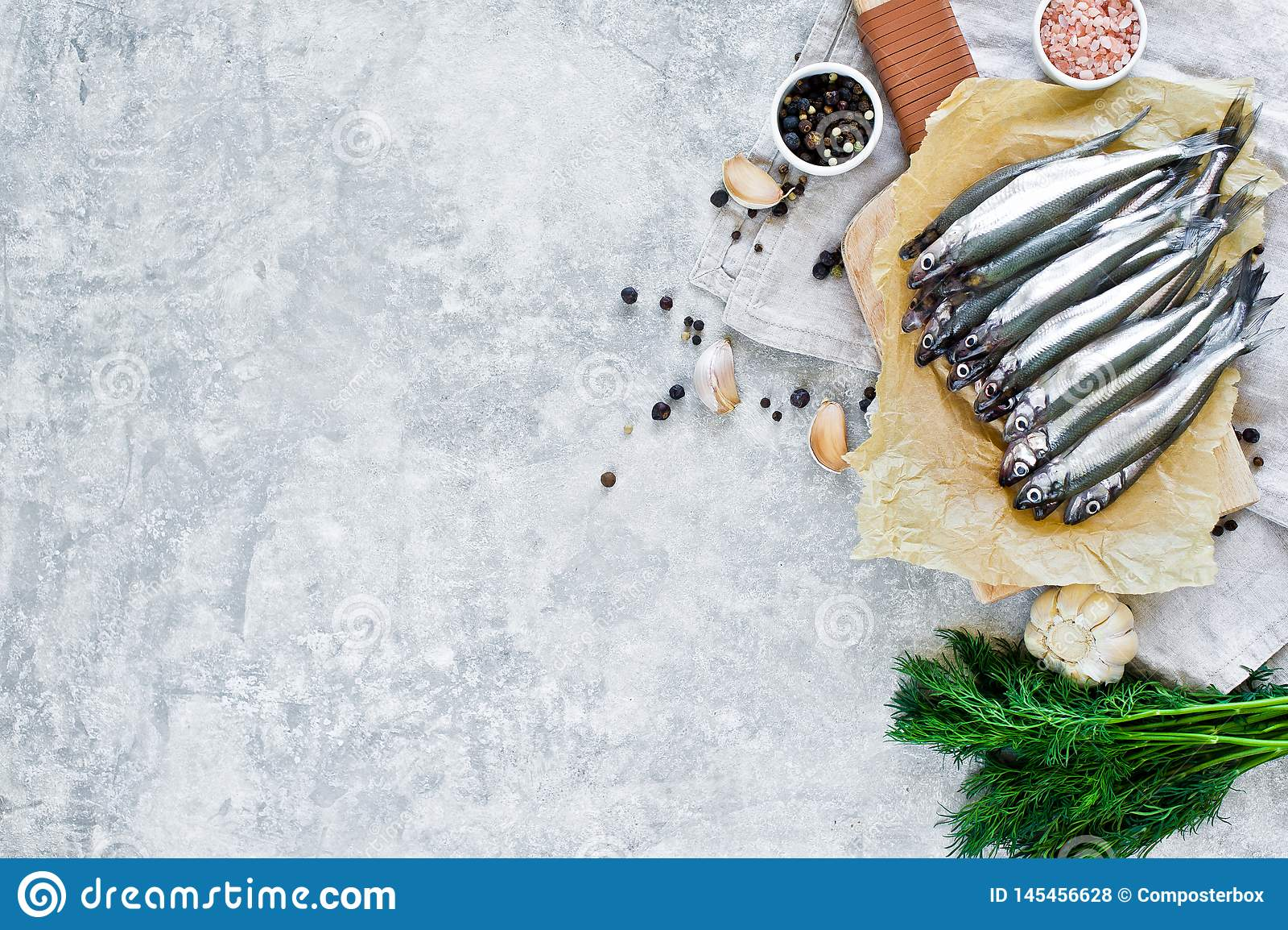 Surowy wytapia na ciapanie desce, koperze, menchii soli, pieprzu i czosnku drewnianych, Szary t?o, odg?rny widok, przestrze? dla