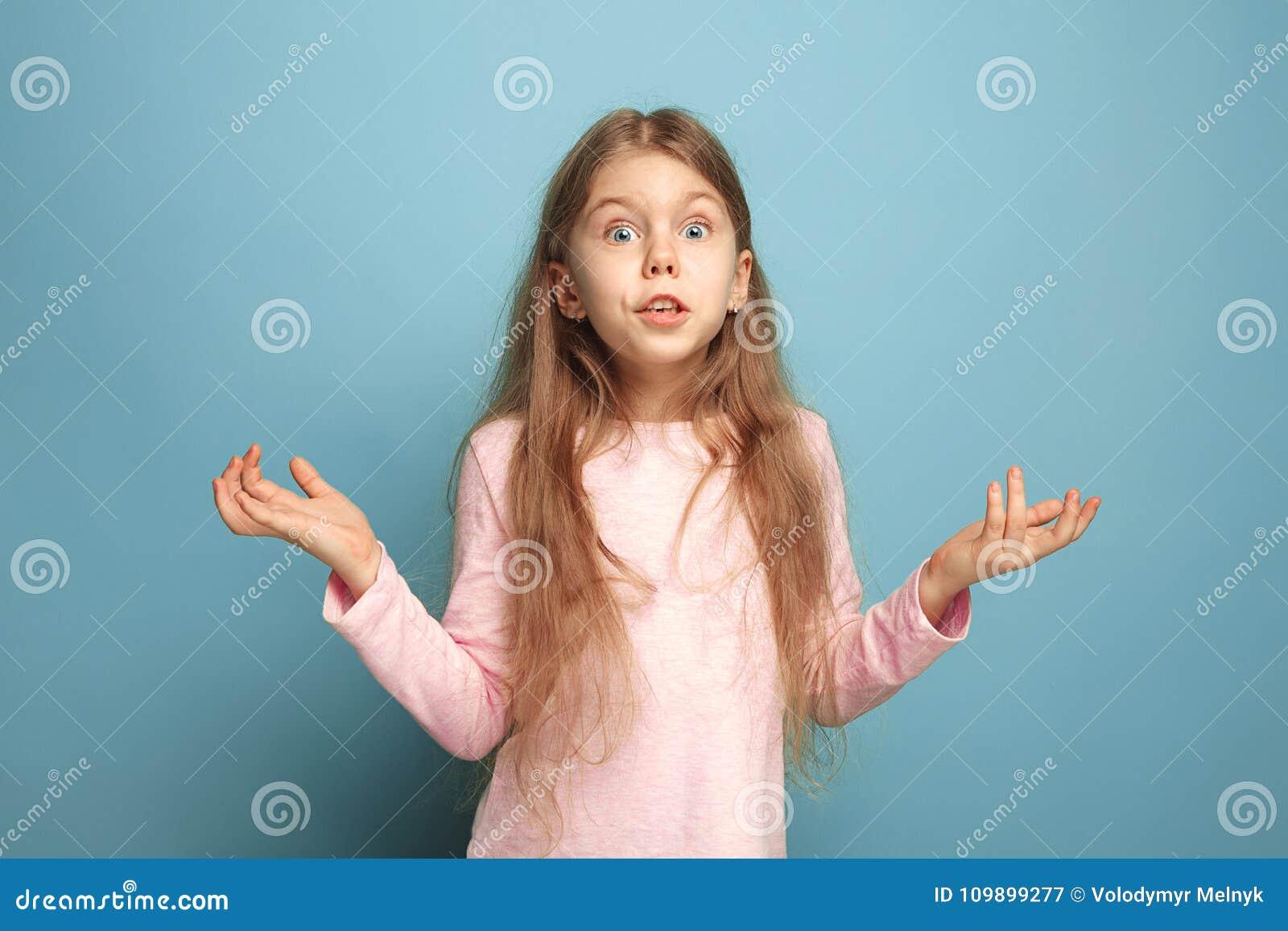 A surpresa, a felicidade, a alegria, a vitória, o sucesso e a sorte Menina adolescente em um fundo azul Expressões faciais e povo