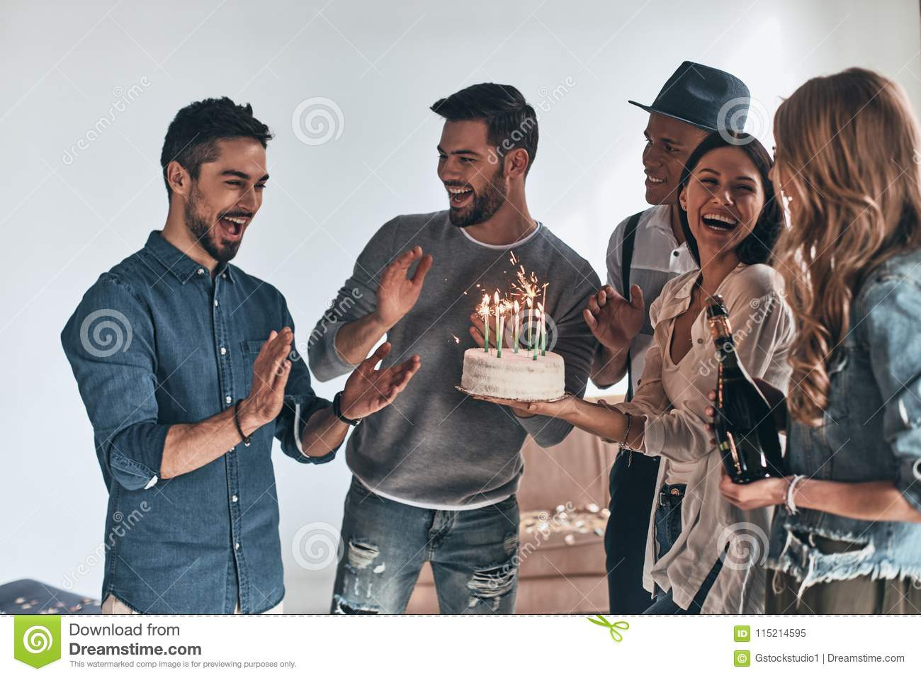 Surprise! Happy young man gesturing and smiling while celebrating birthday among friends
