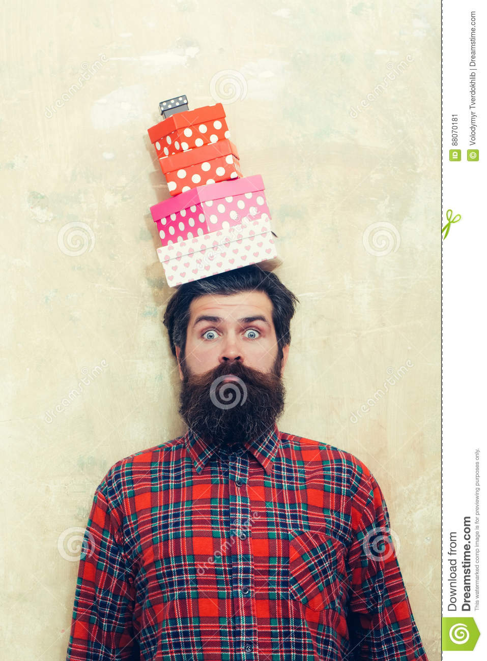 Surprised bearded man holding colorful gift boxes stacked on head