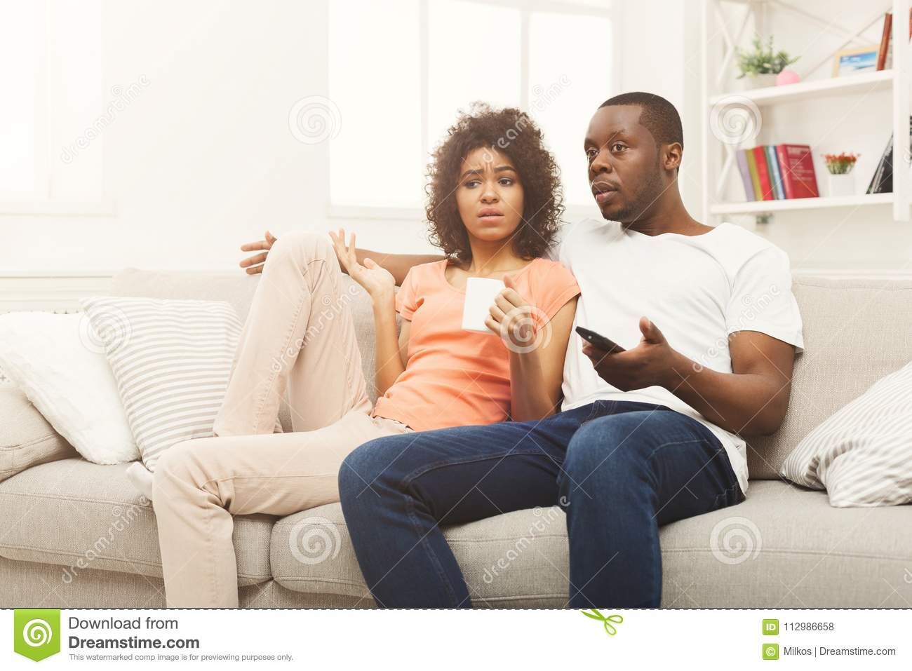 Surprised black couple watching TV at home