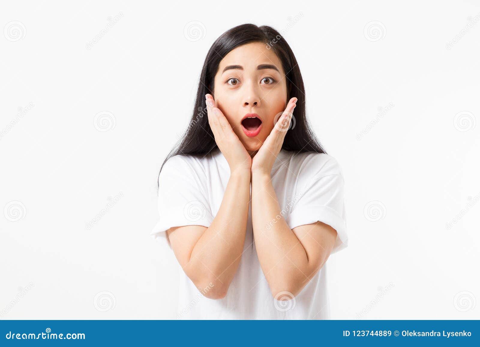 Surprised chocou a cara asiática entusiasmado da mulher isolada no fundo branco Menina asiática nova na camisa do verão t Copie o