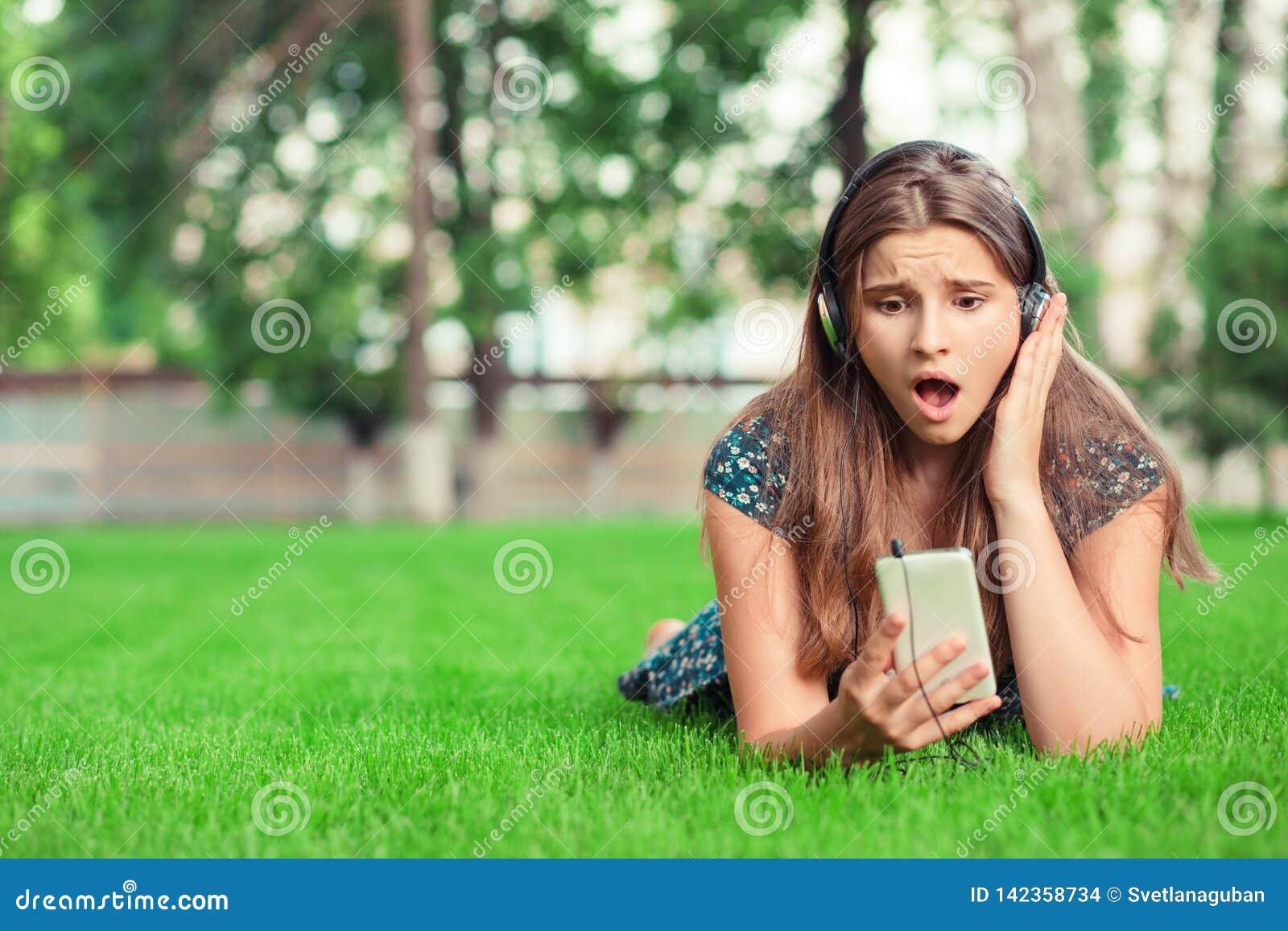 Surprised chocou a jovem mulher que olha o telefone