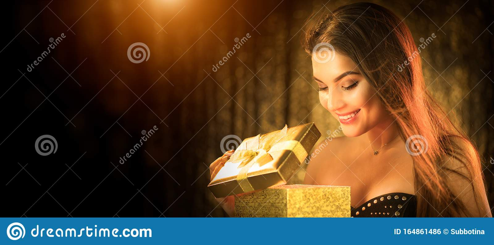 Surprised Christmas Winter Woman opening magic Christmas Gift box and smiling. Fairy tale. Beautiful New Year and Xmas scene