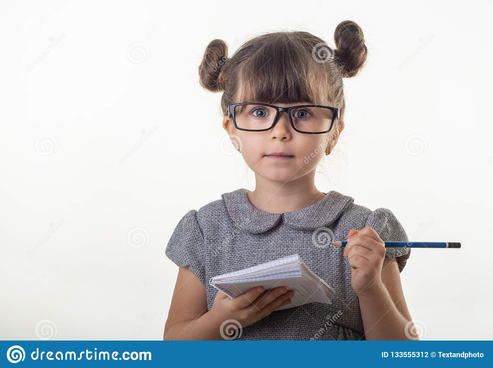 Surprised cute child in eyeglasses, writing in notebook using pencil, keeping mouth wide open.