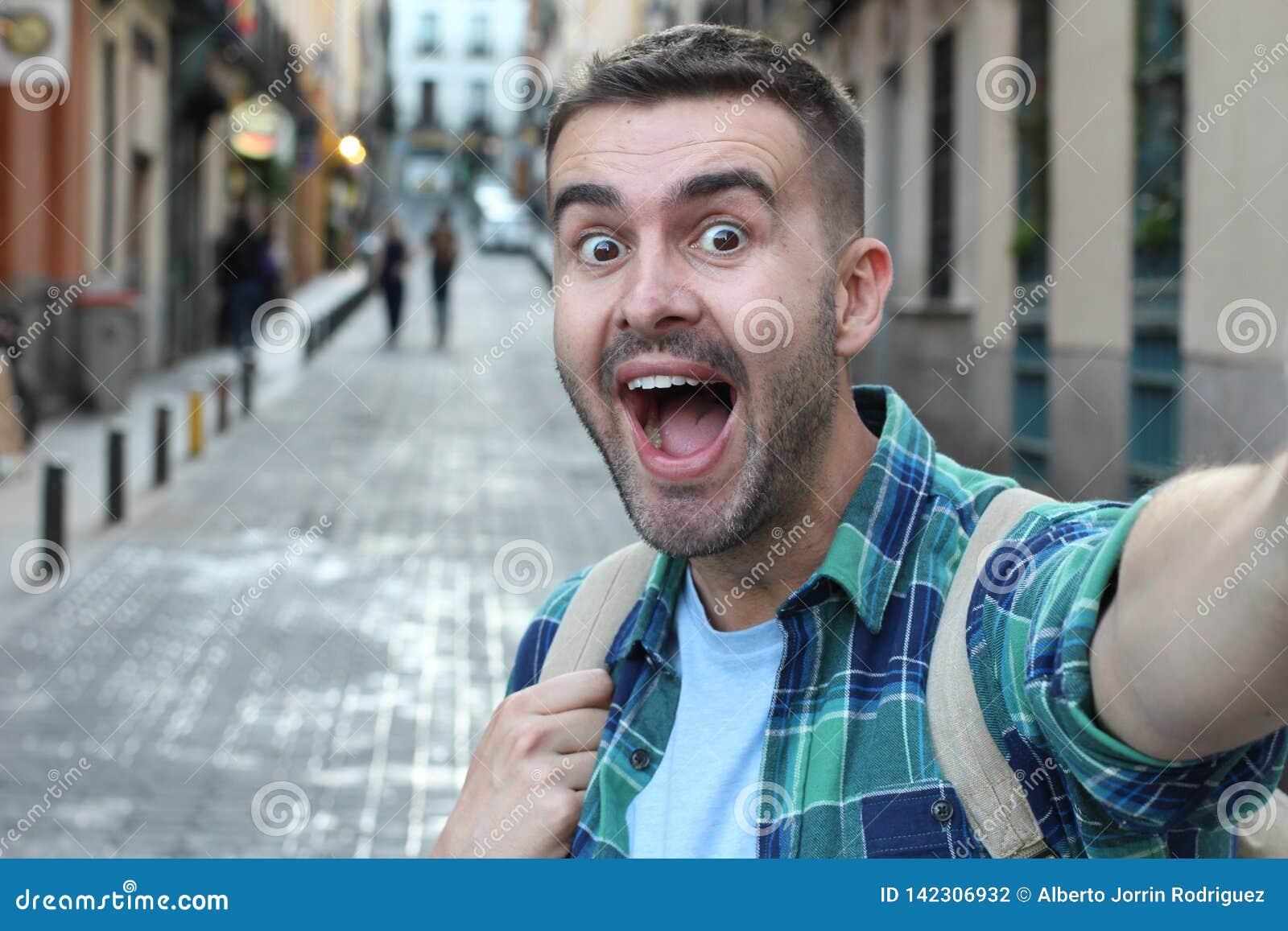 Surprised ecstatic man taking a selfie