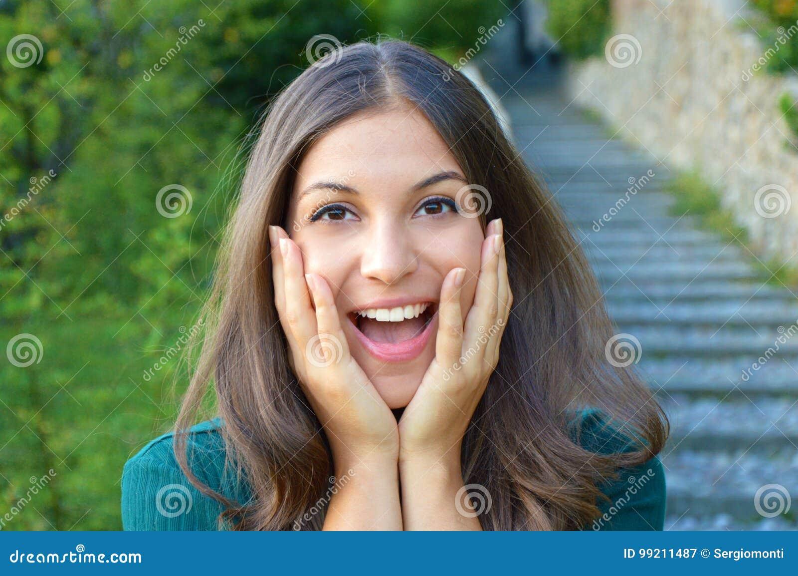 Surprised a excité la jeune femme tenant son sourire d apparence de visage