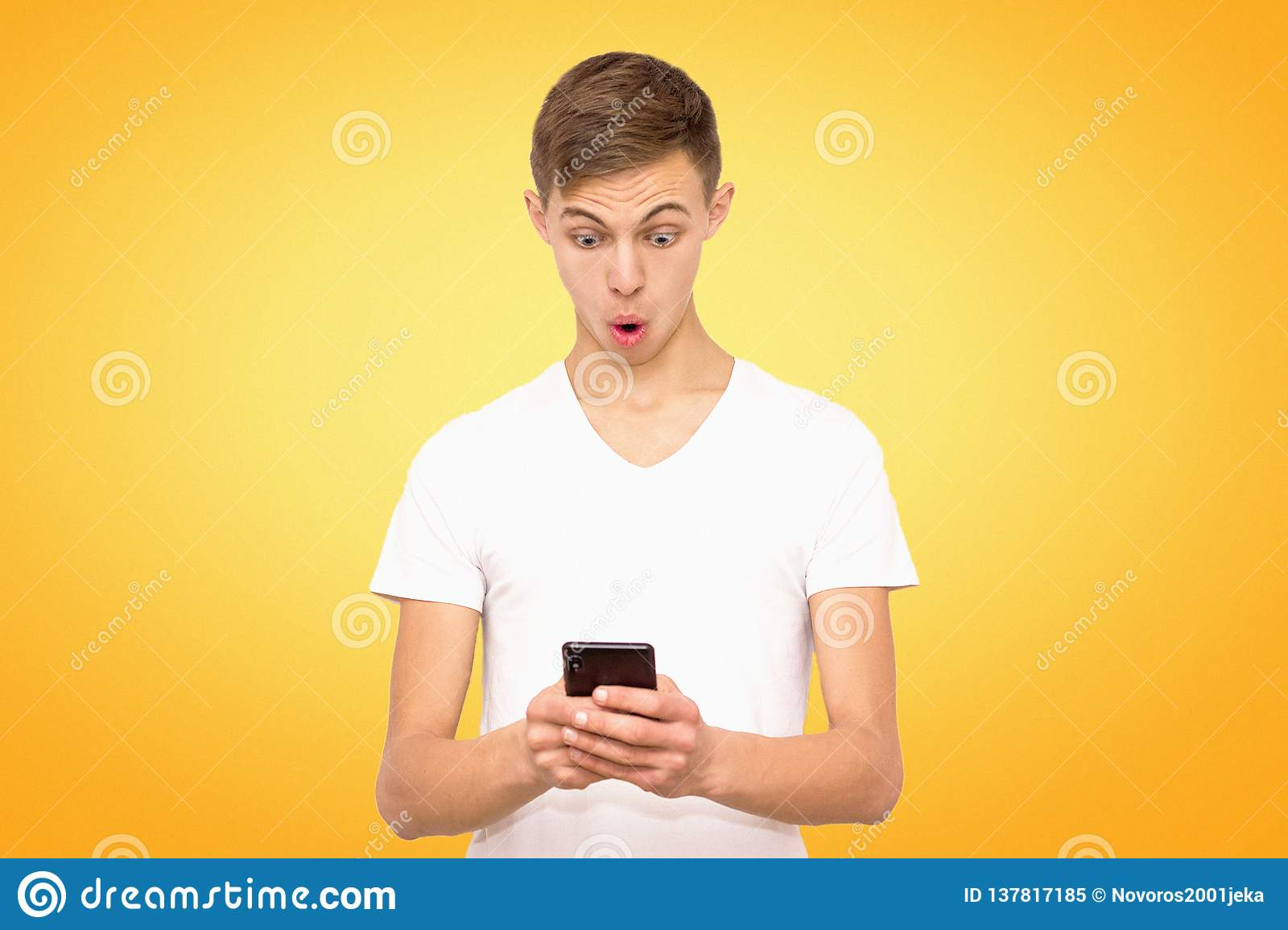 Surprised guy in white t-shirt with telephone, isolate, man on yellow background