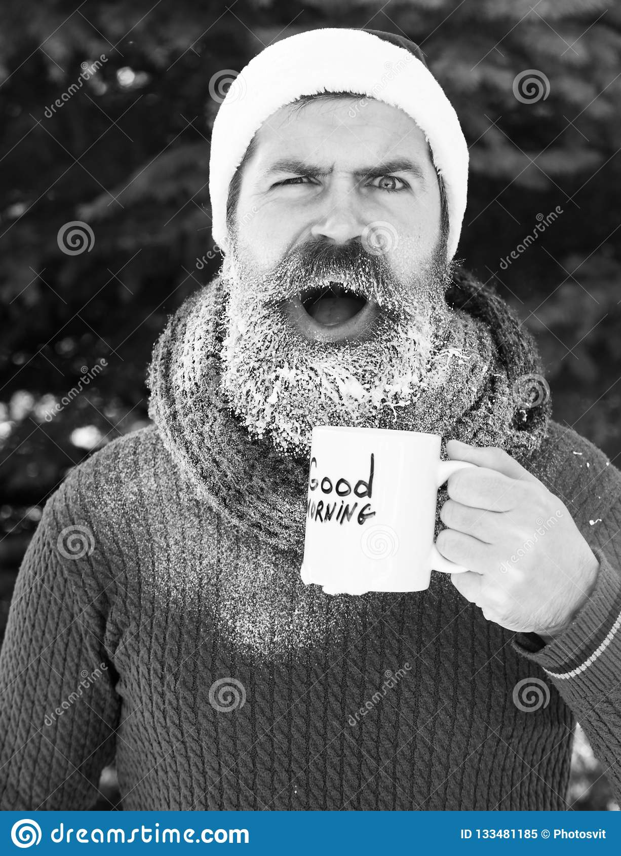 Surprised handsome man in santa claus hat, bearded hipster with beard and moustache drinks from cup with good morning