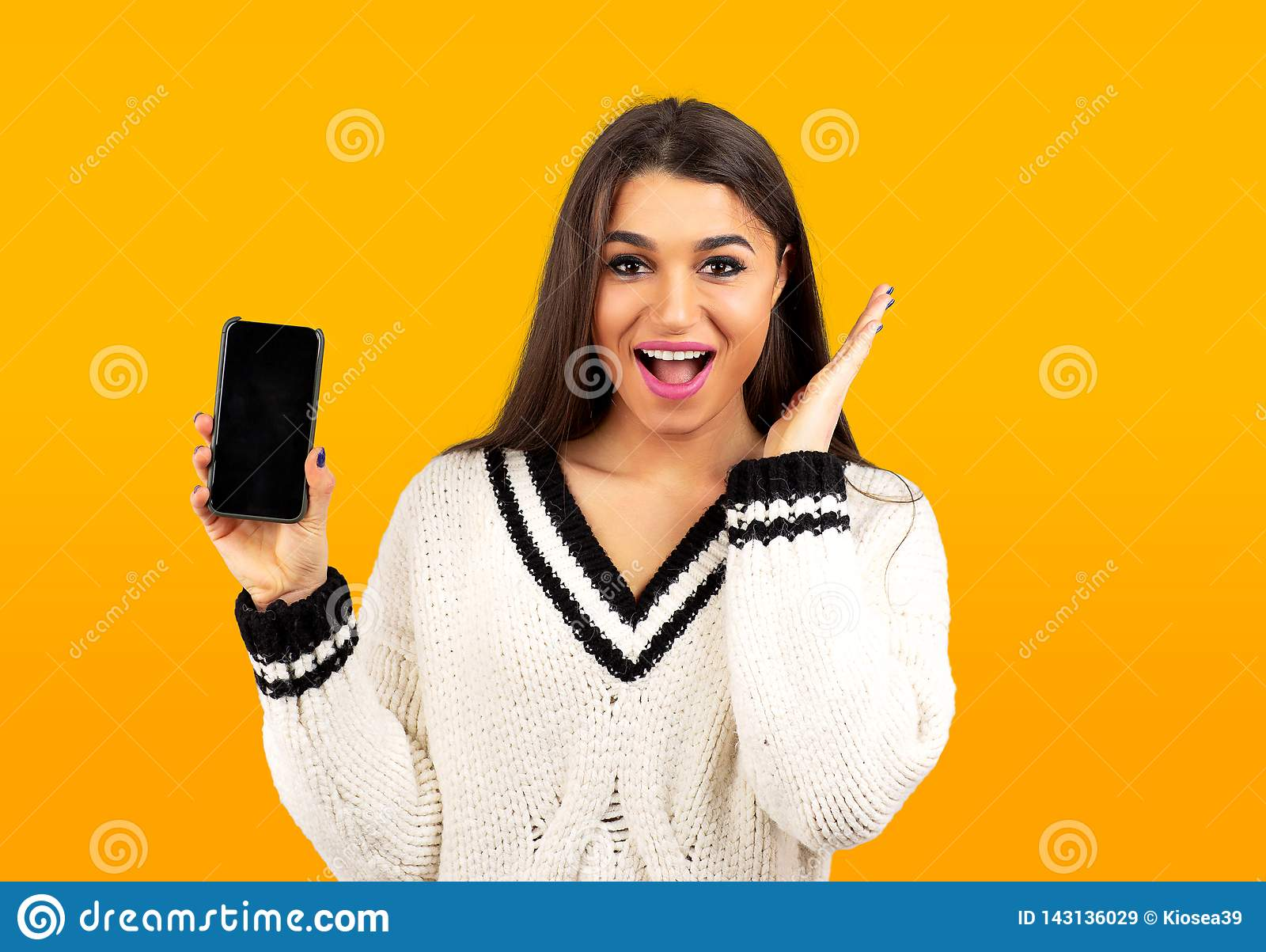 Surprised happy woman in white sweater showing a new smartphone